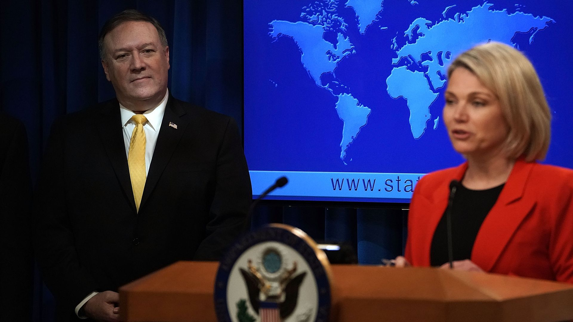 State Dept spokeswoman Heather Nauert speaks at a podium while Mike Pompeo watches from behind
