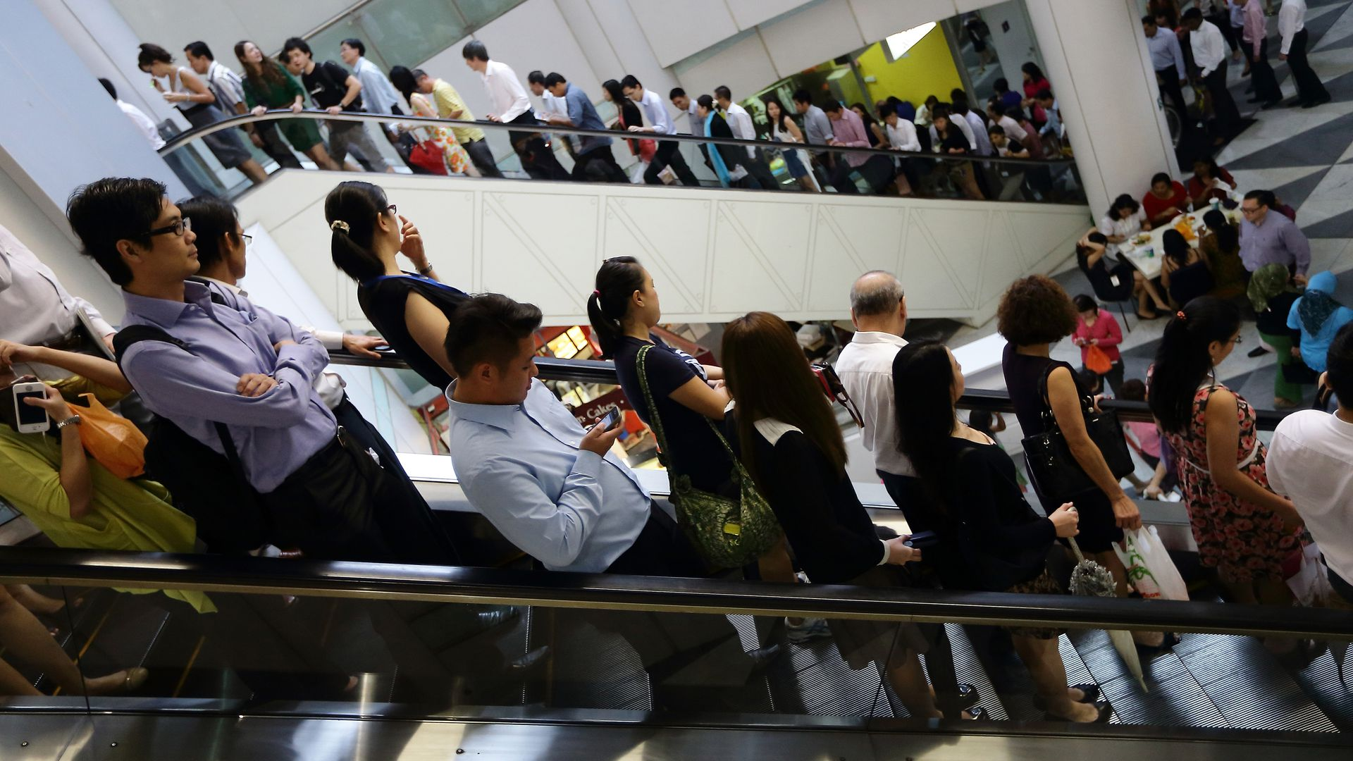 Commuters line the escalators at lunch hour at Raffles Place in Singapore