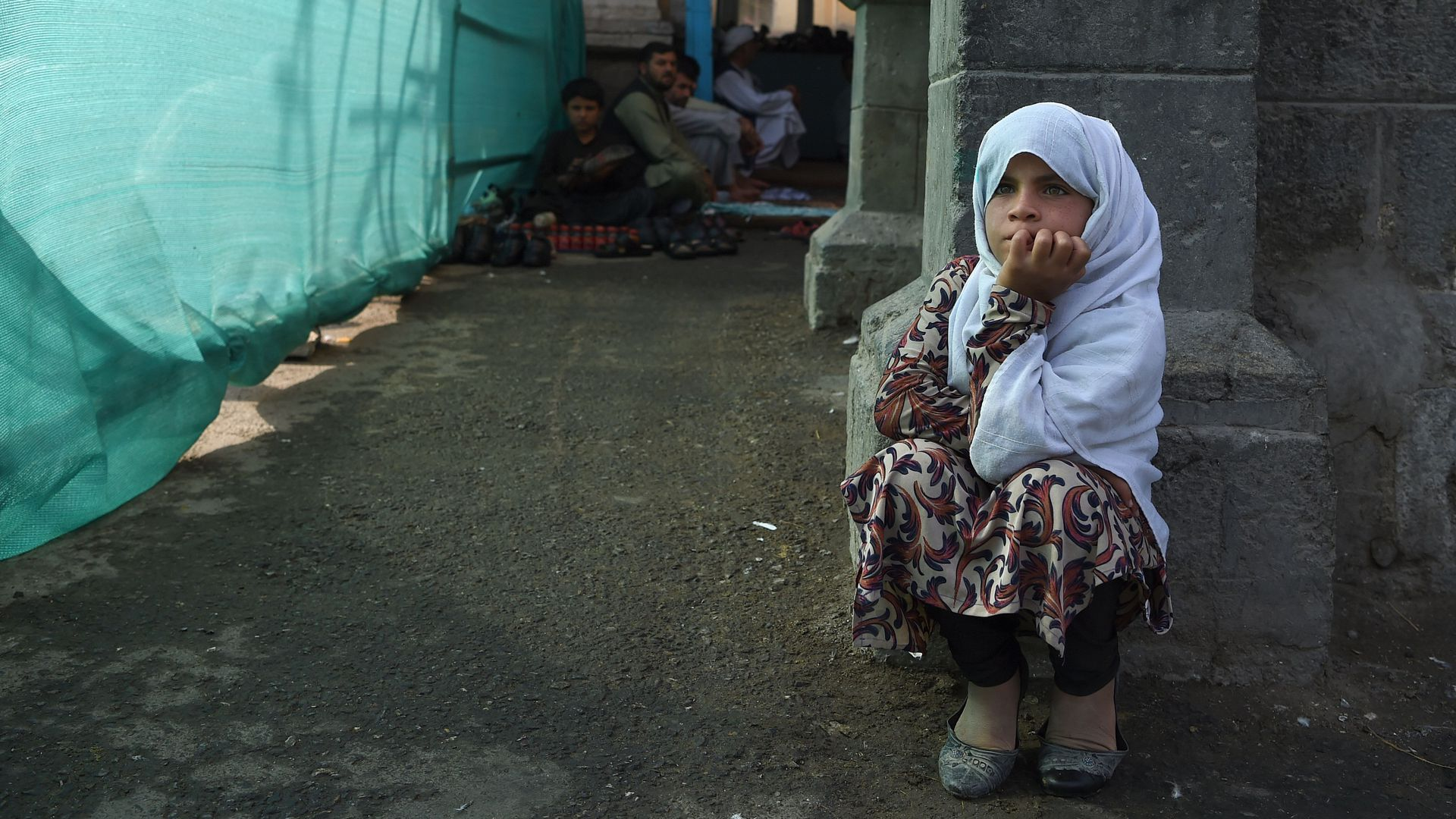 An Afghan girl looks on as she begs for alms.