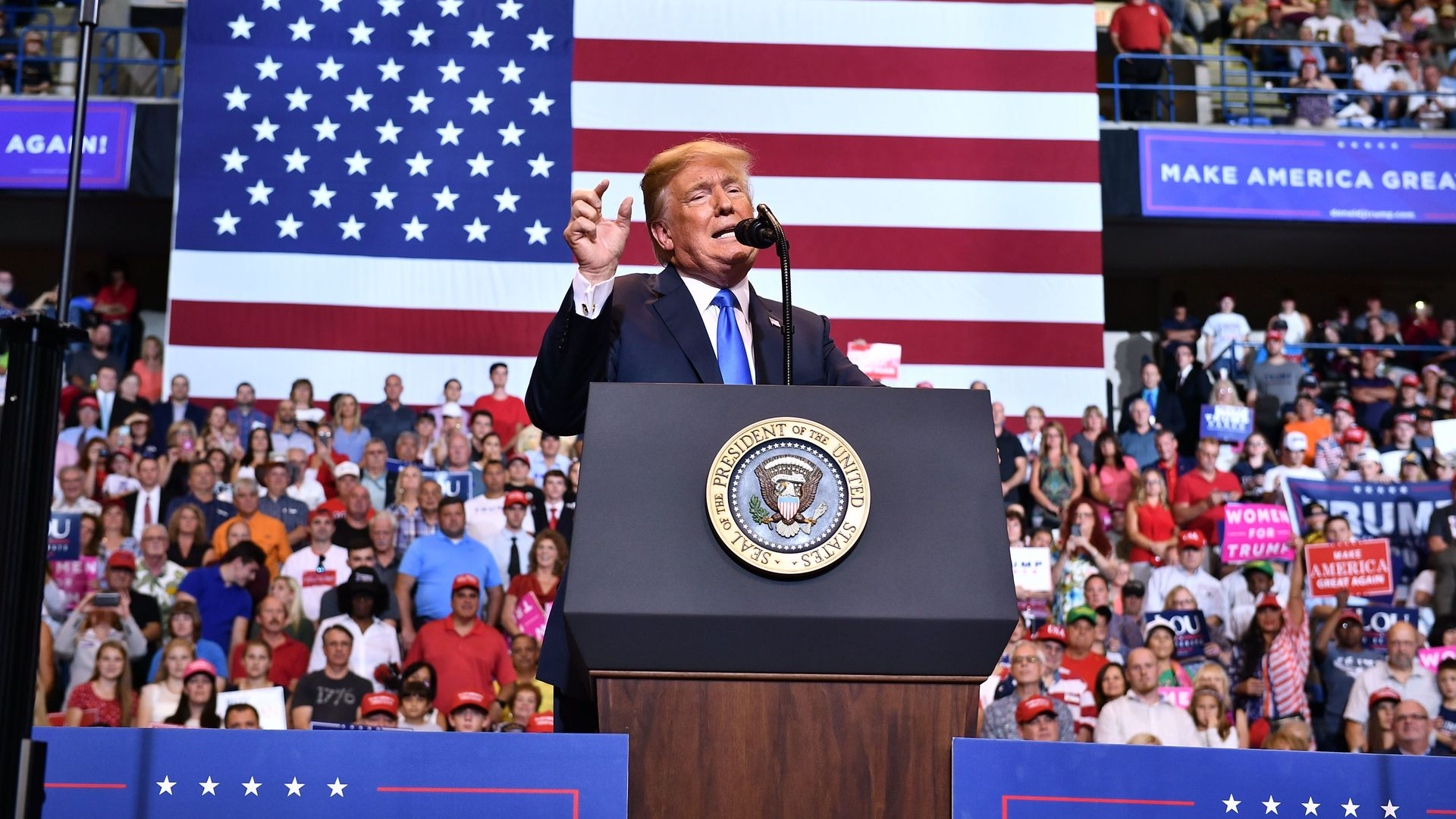 Donald Trump speaks from a podium, in front of a crowd and large American flag