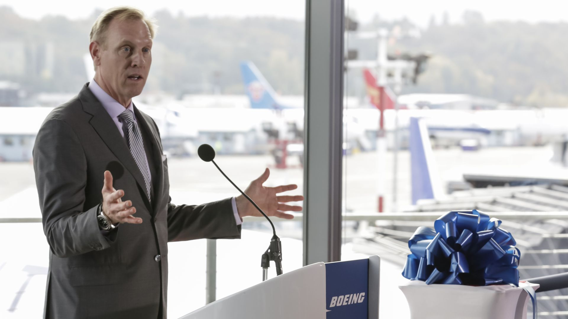 In this image, Pat Shanahan speaks in front of a microphone and podium. The windows behind him look out onto an airport.