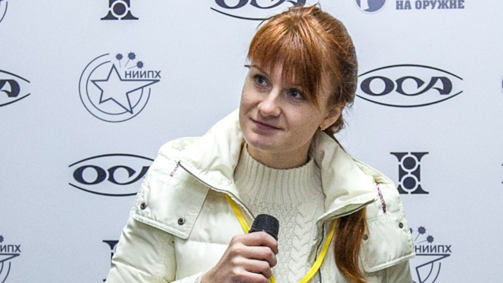 In this image, Maria Butina speaks into a microphone.