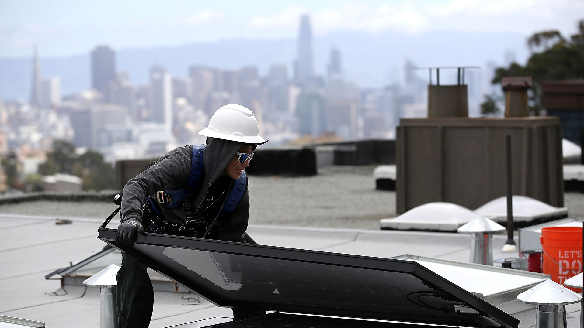 Luminalt solar installers Pam Quan moves a solar panel during an istallation on the roof of a home on May 9, 2018 in San Francisco, California.