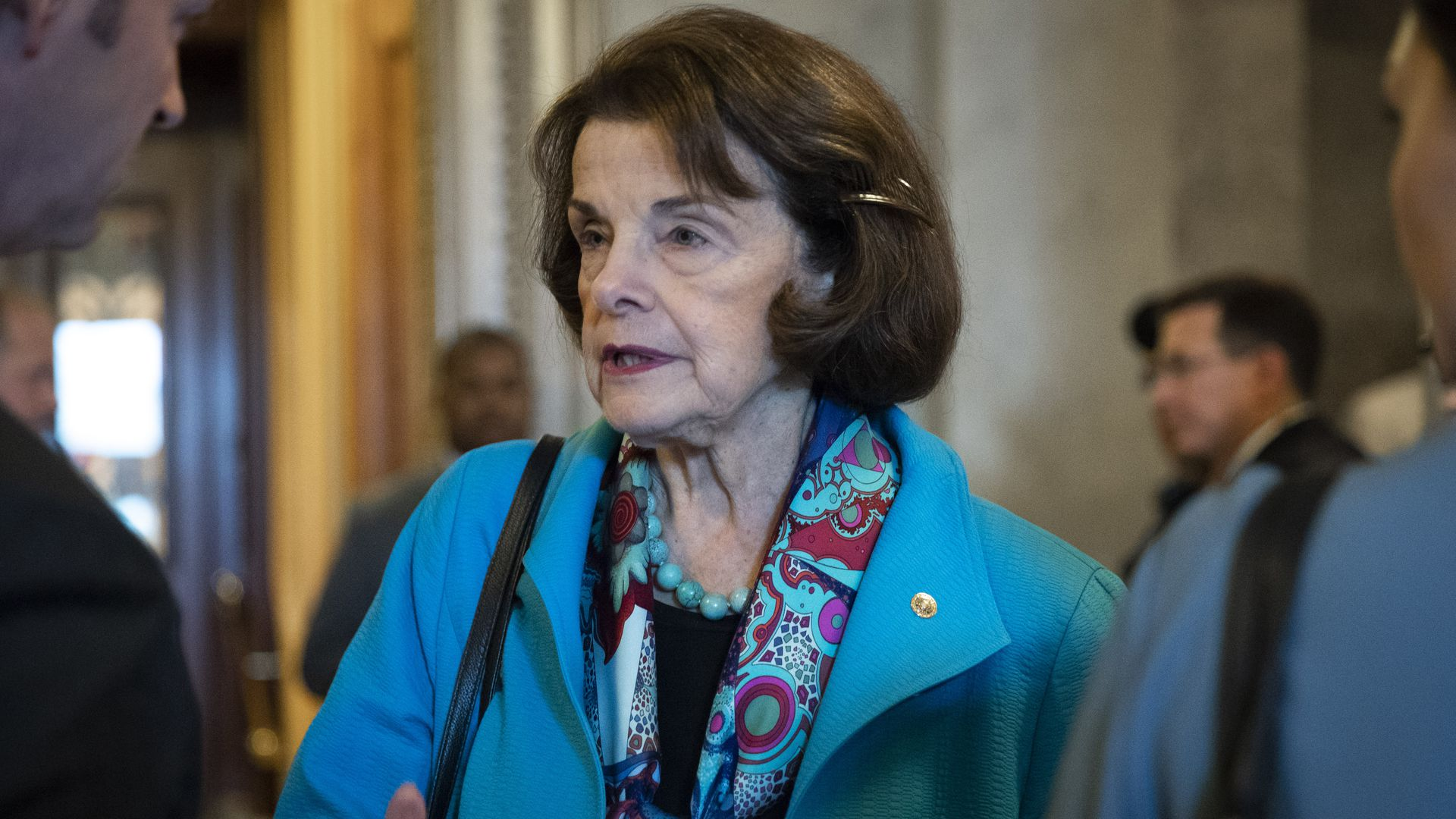 In this image, Dianne Feinstein wears a bright blue coat and speaks to reporters.