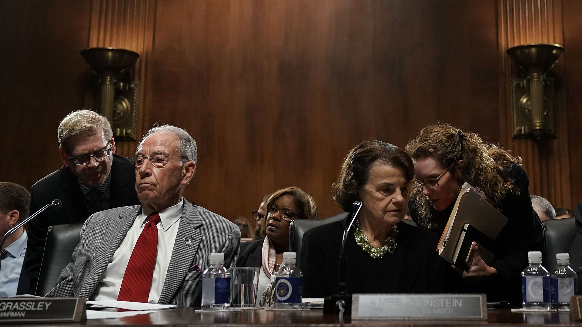 Chuck Grassley and Dianne Feinstein talking to their aides in a briefing room.