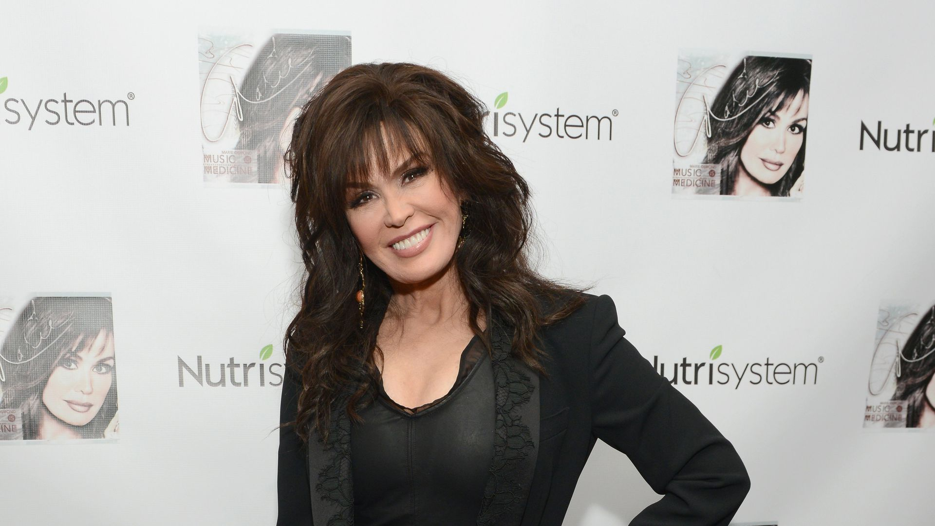 Marie Osmond poses for a photo with Nutrisystem logos in the background.