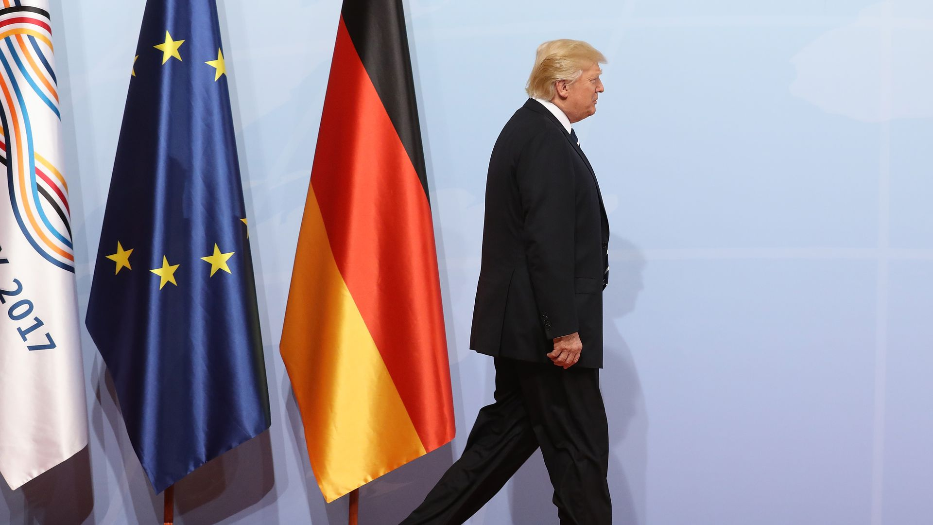 Trump walks past the German and EU flags