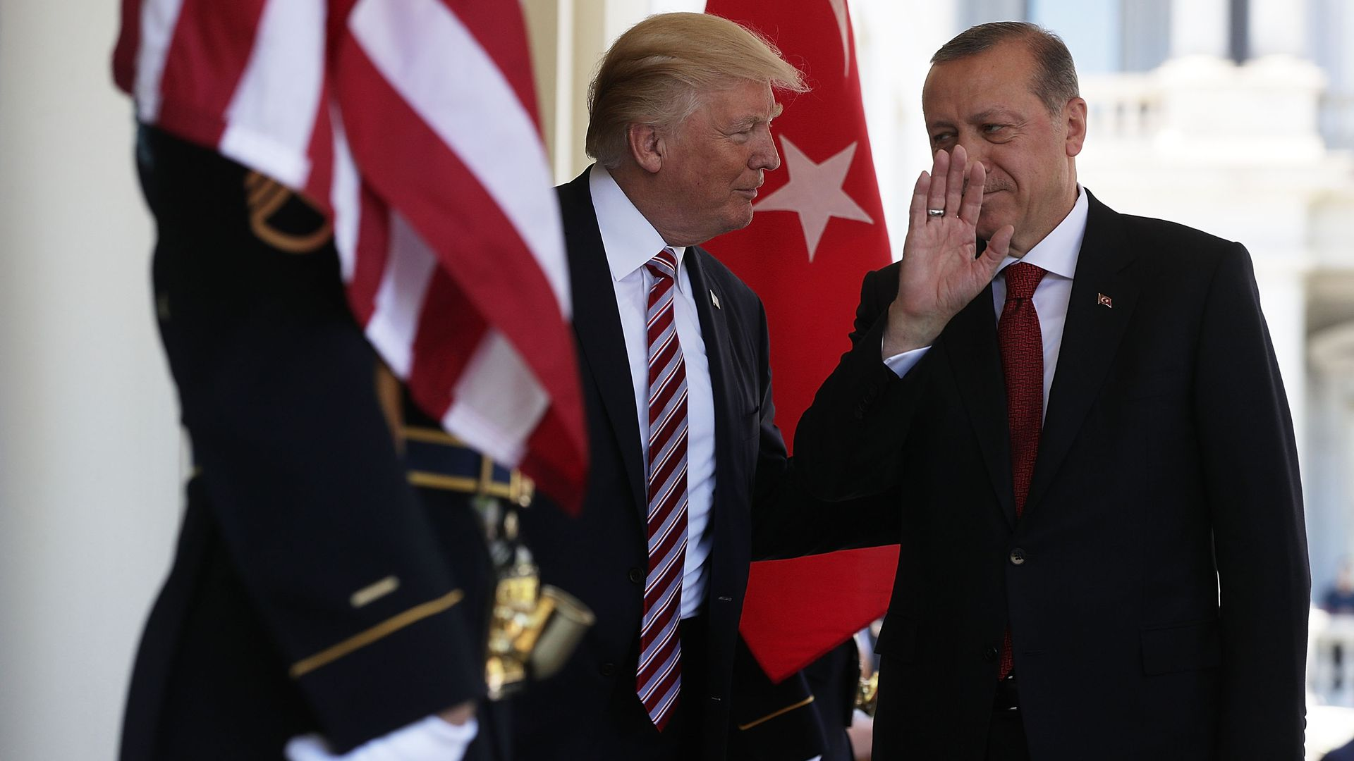 In this image, Trump and the Turkish president speak to each other behind flags