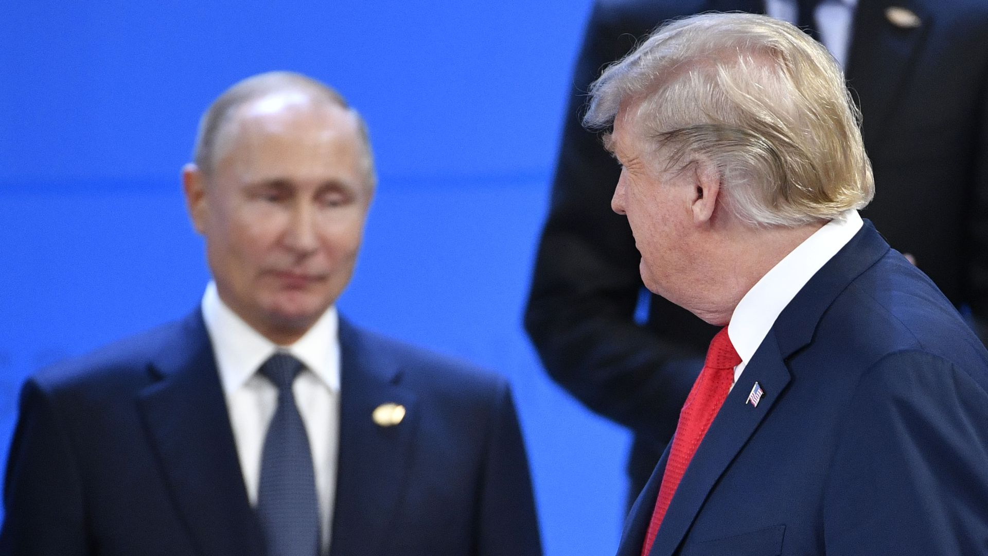 In this image, Trump walks by Putin and smiles at him.