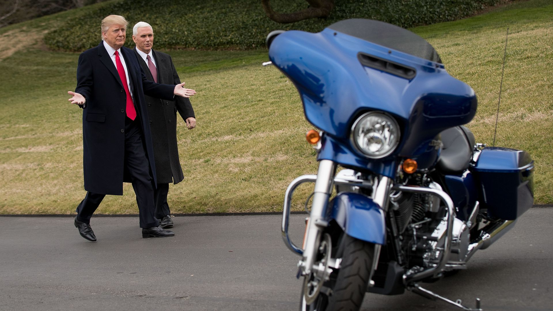 President Trump and VP Pence approach a Harley-Davidson motorcycle.