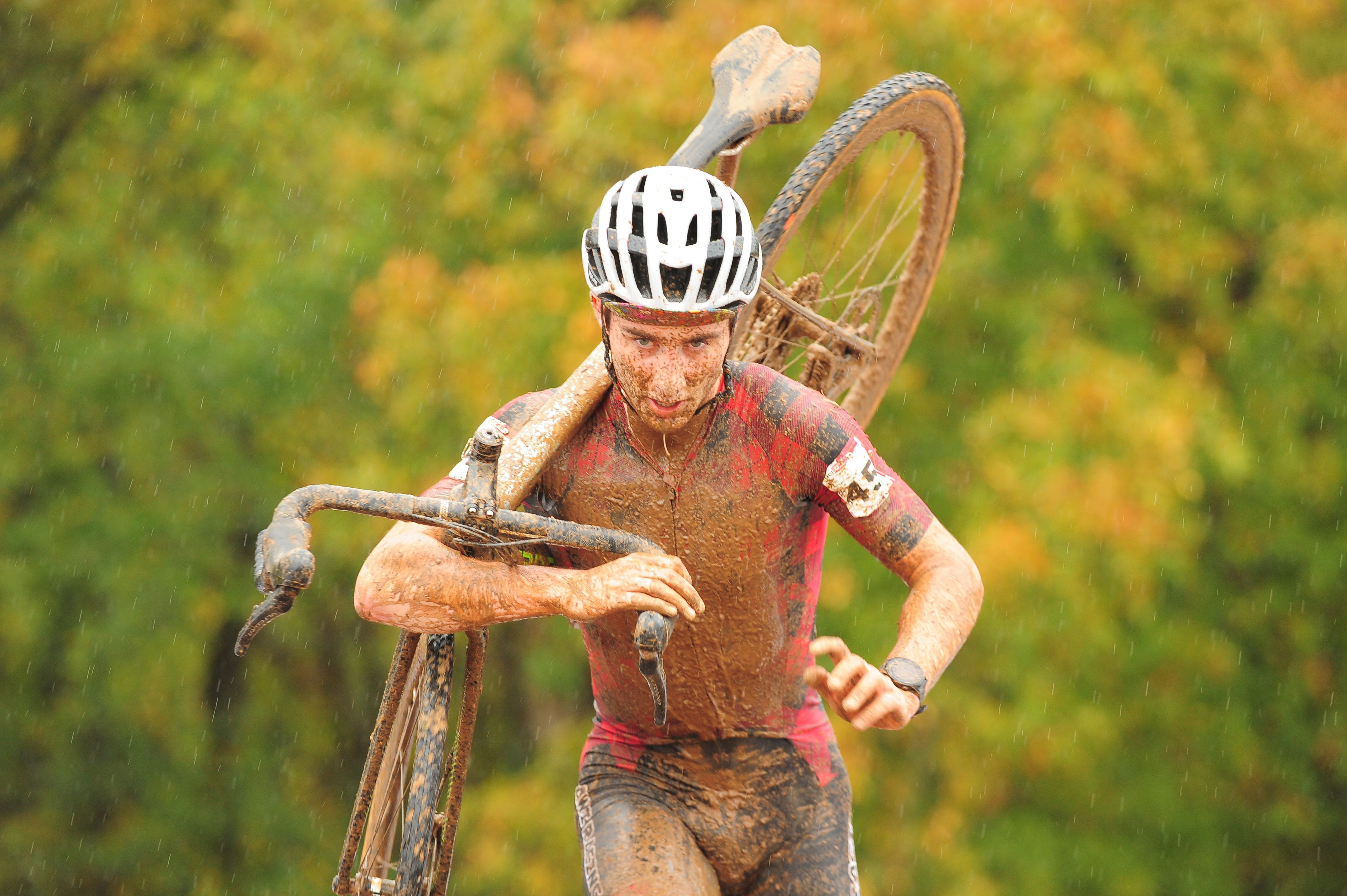 Muddy man carrying a bike up a set of stairs in the rain.
