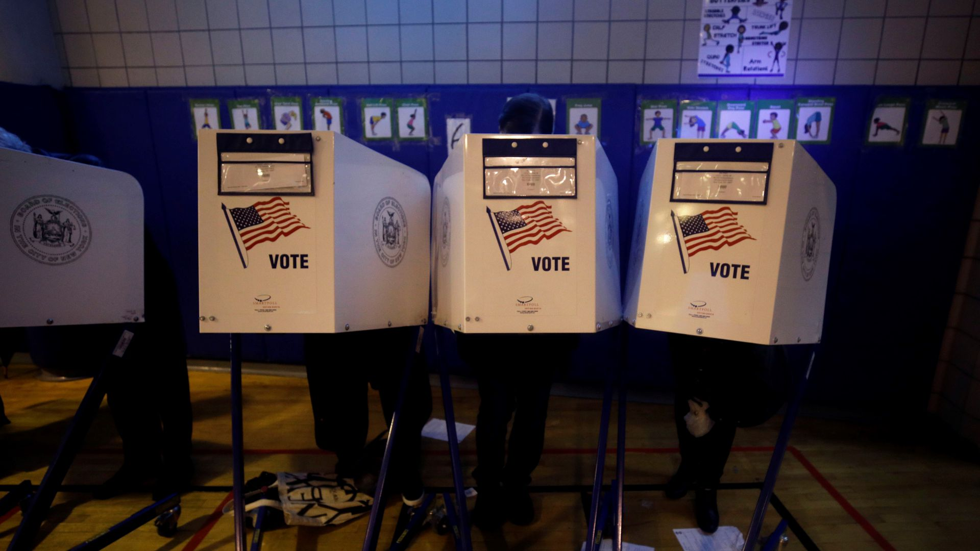 In this image, three people stand behind three different white voting booths. Each booth has an American flag on it.