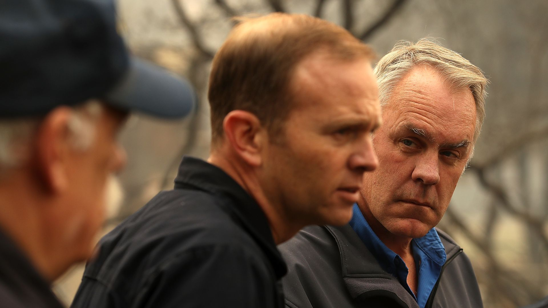 Ryan Zinke and two other men talking.