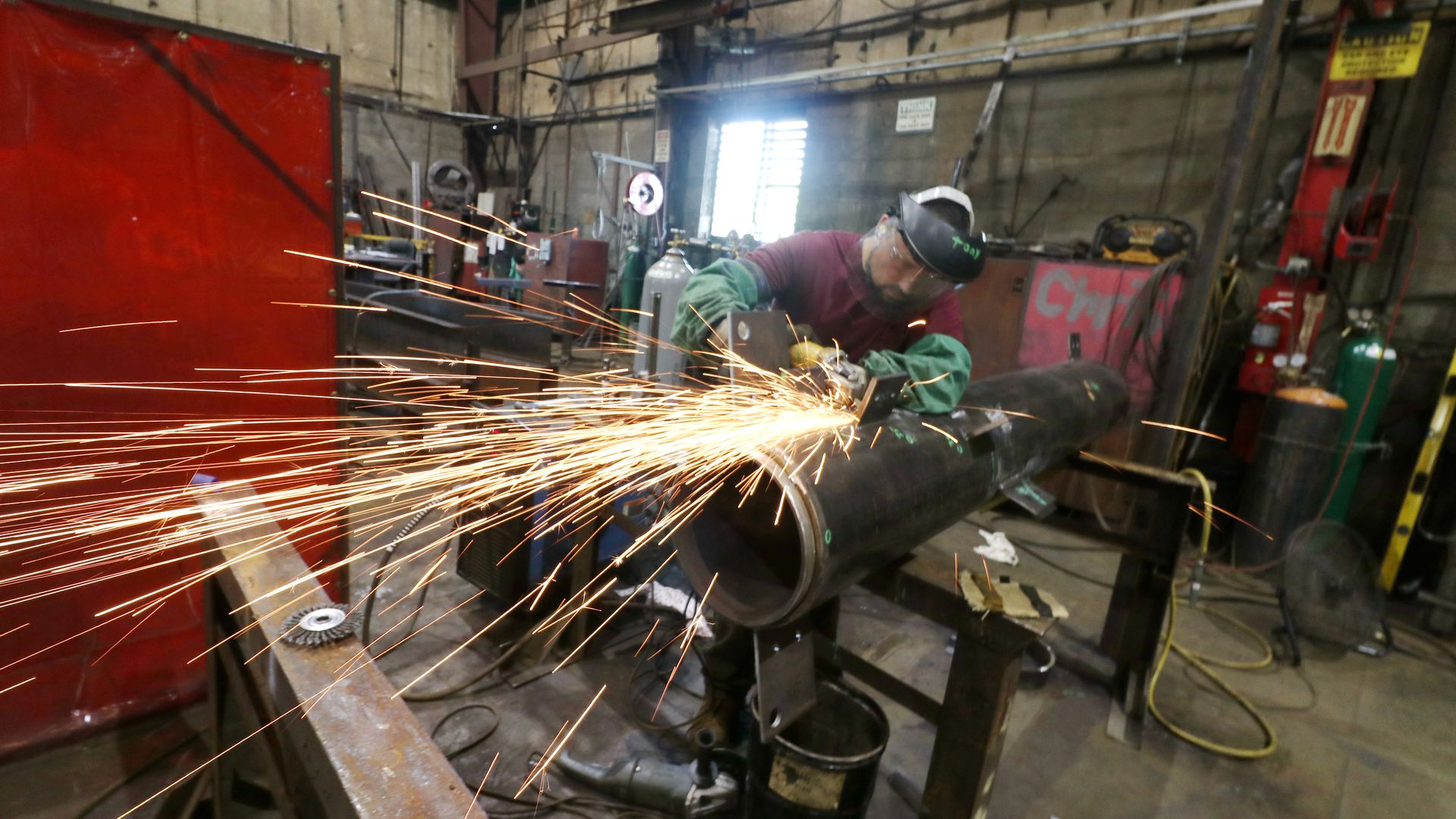 A man using an angle grinder on steel.