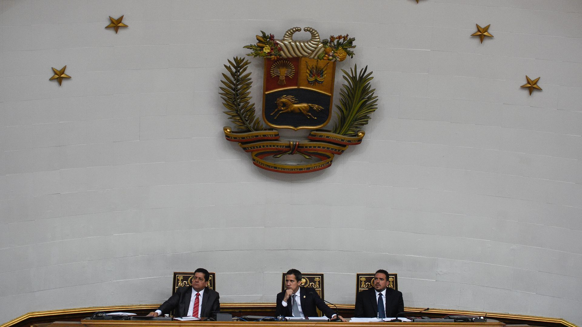 Juan Guaido sits with two other men at the National Assembly in Venezuela.