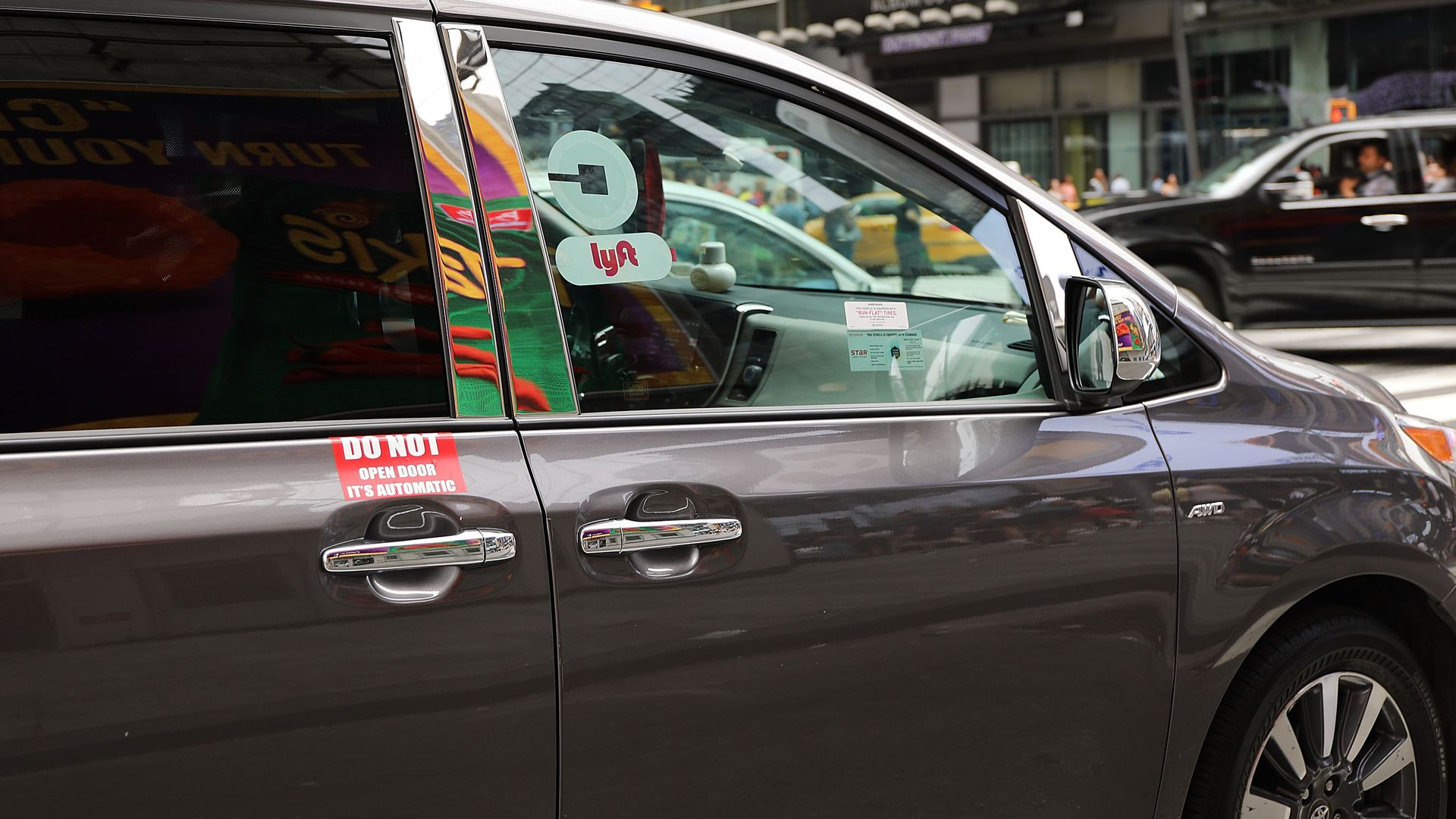A van with Lyft and Uber window stickers moves through traffic in Manhattan
