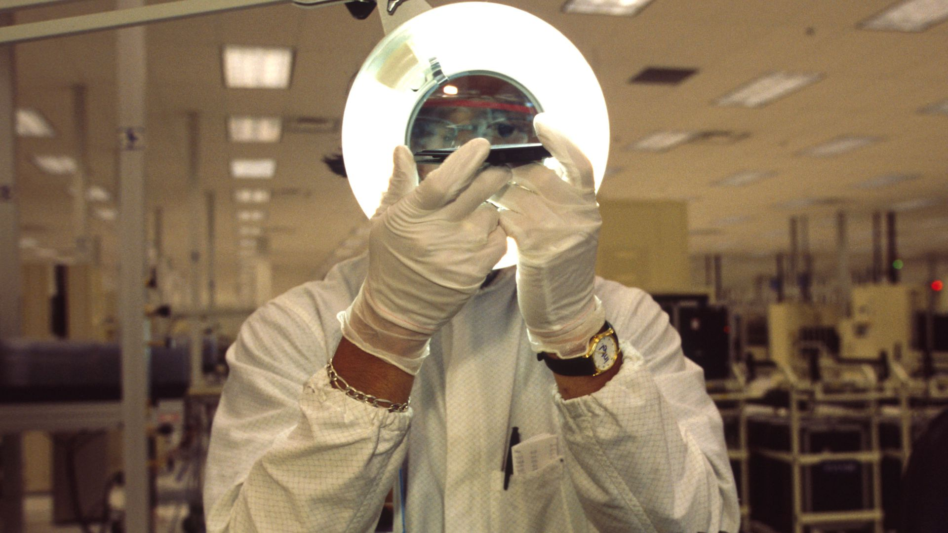 Photo of a man holding up a computer chip to a light