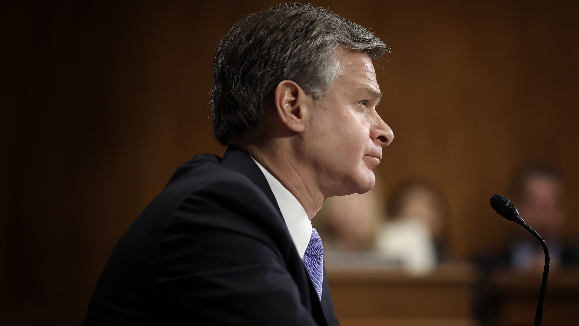Wray sitting in his chair, facing the committee.