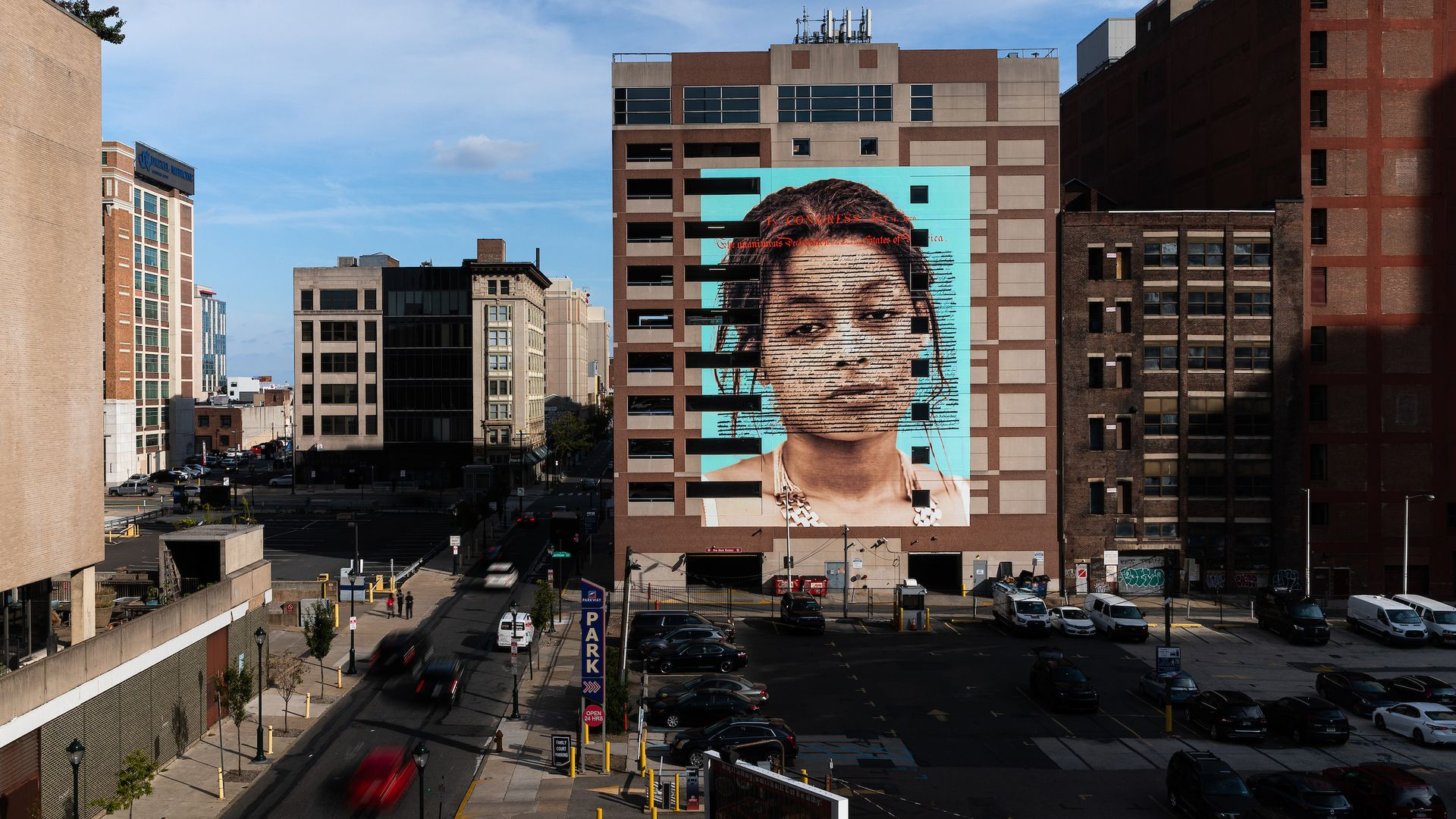 """The mural """"Declaration"""" is seen here on a building in North Philadelphia of a woman of color with the Declaration of Independence imposed over her face."""