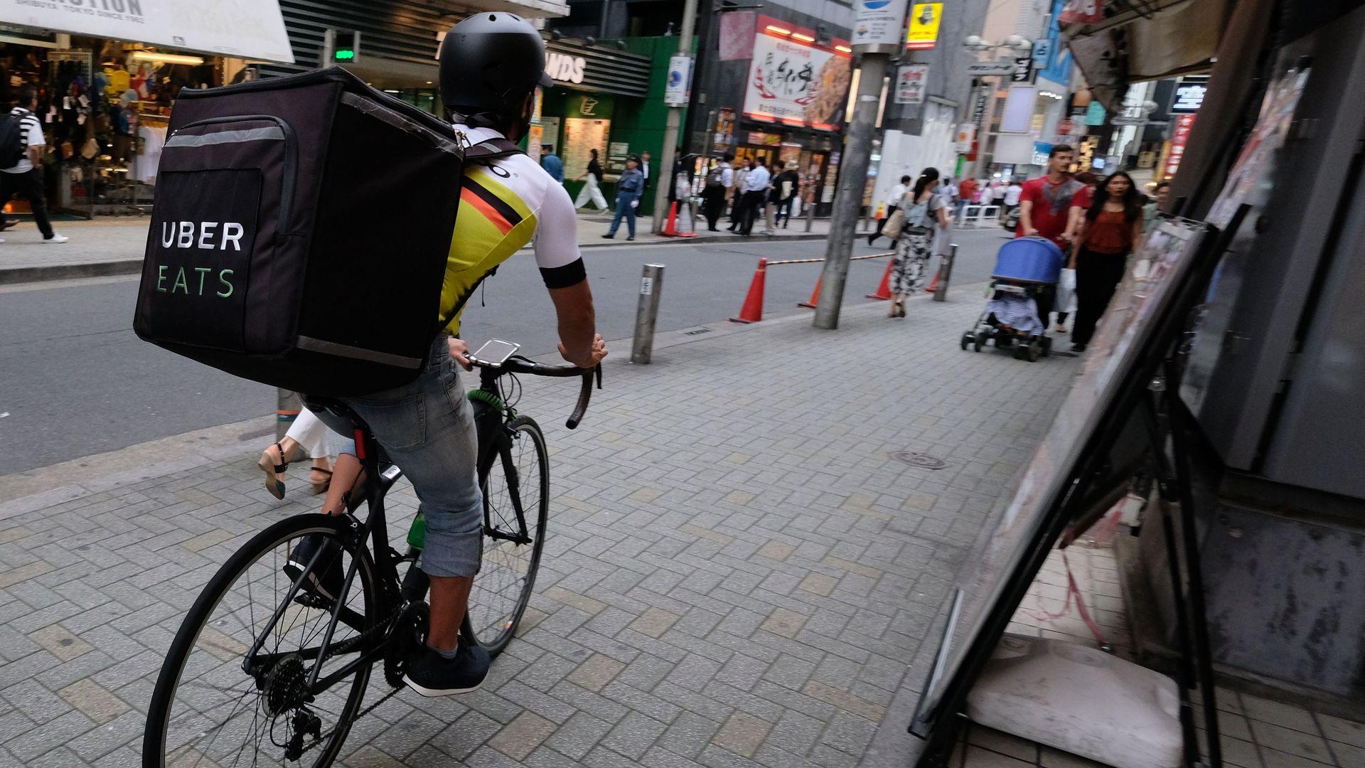 Man on bike delivering food with Uber Eats.