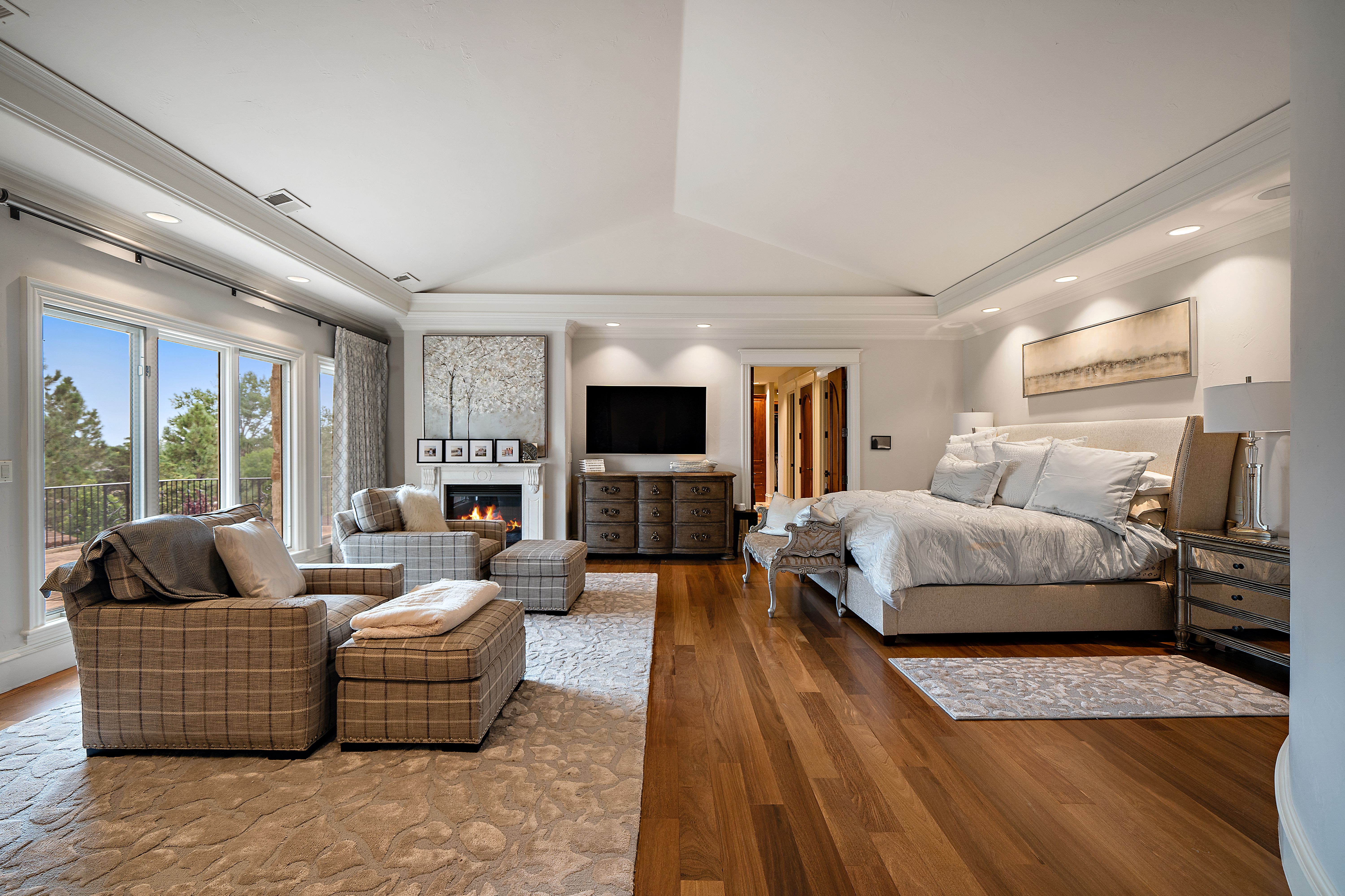 A large bedroom with a fireplace.