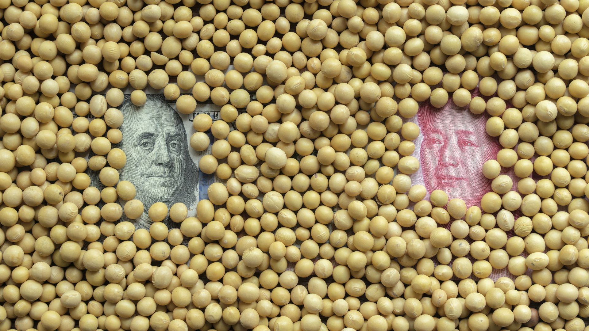 Soybeans covering U.S. dollar bill and China's RMB bill