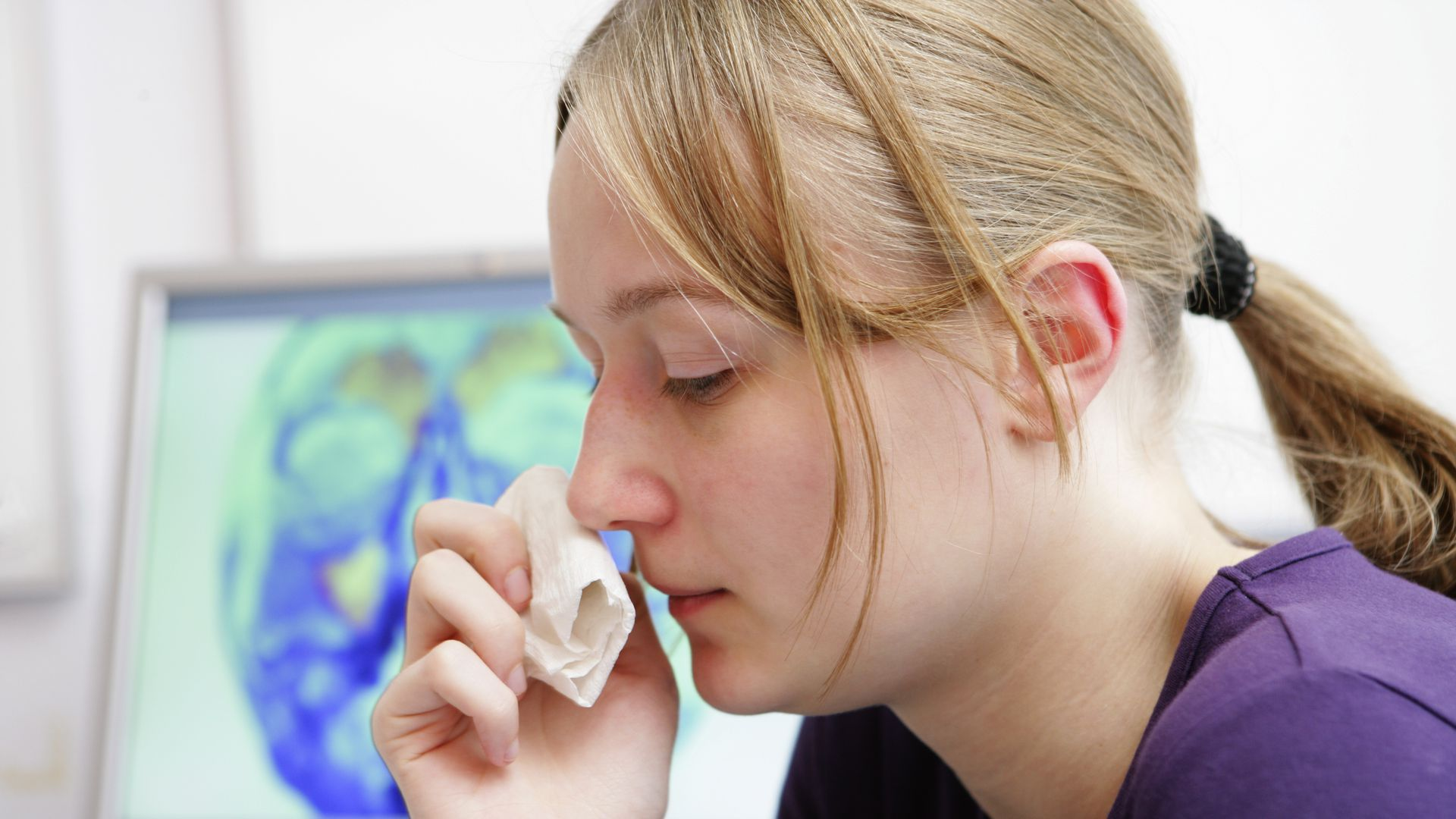 A woman wipes her nose with a tissue.