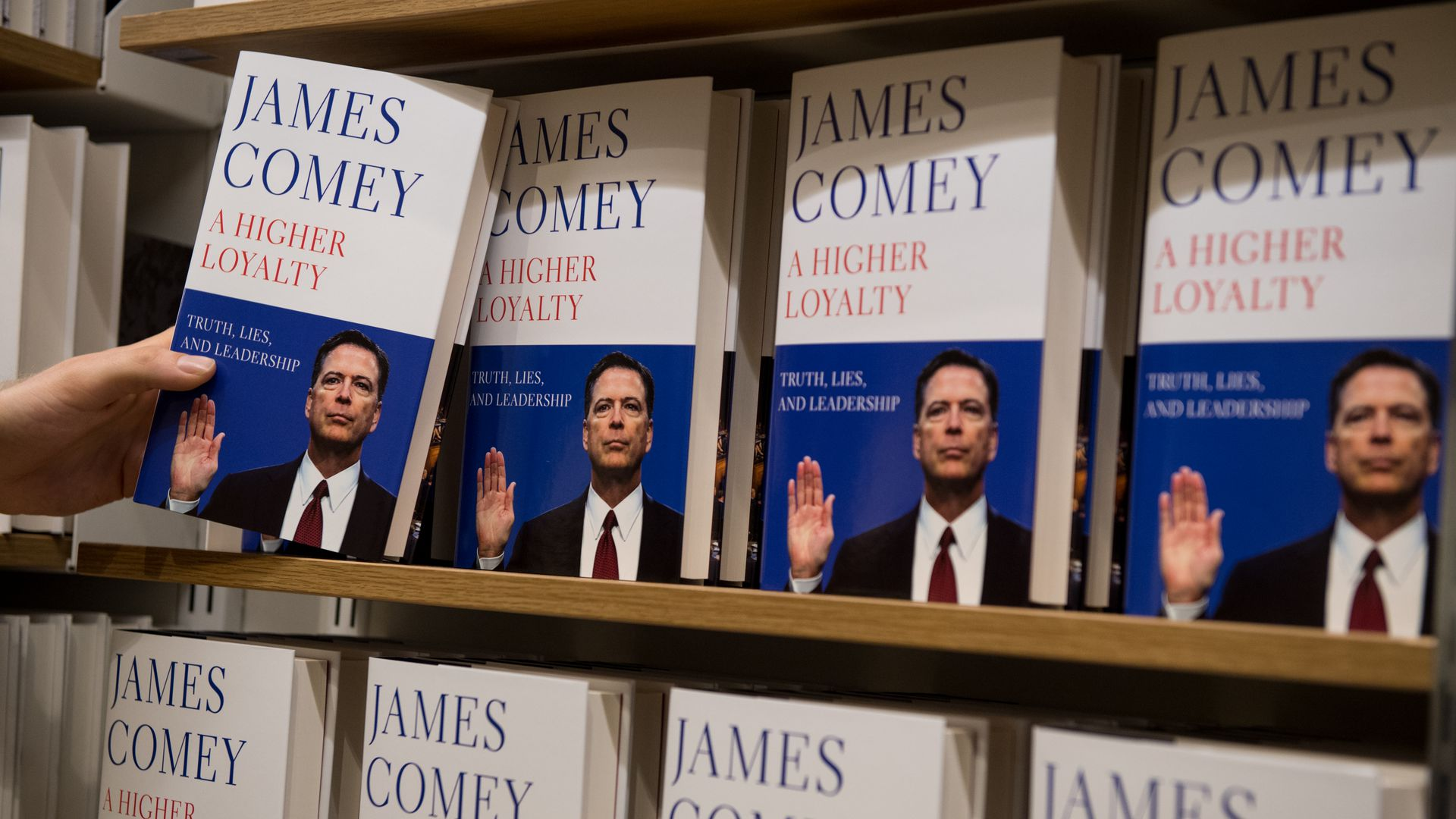 A customer reaches for Comey's book in a store