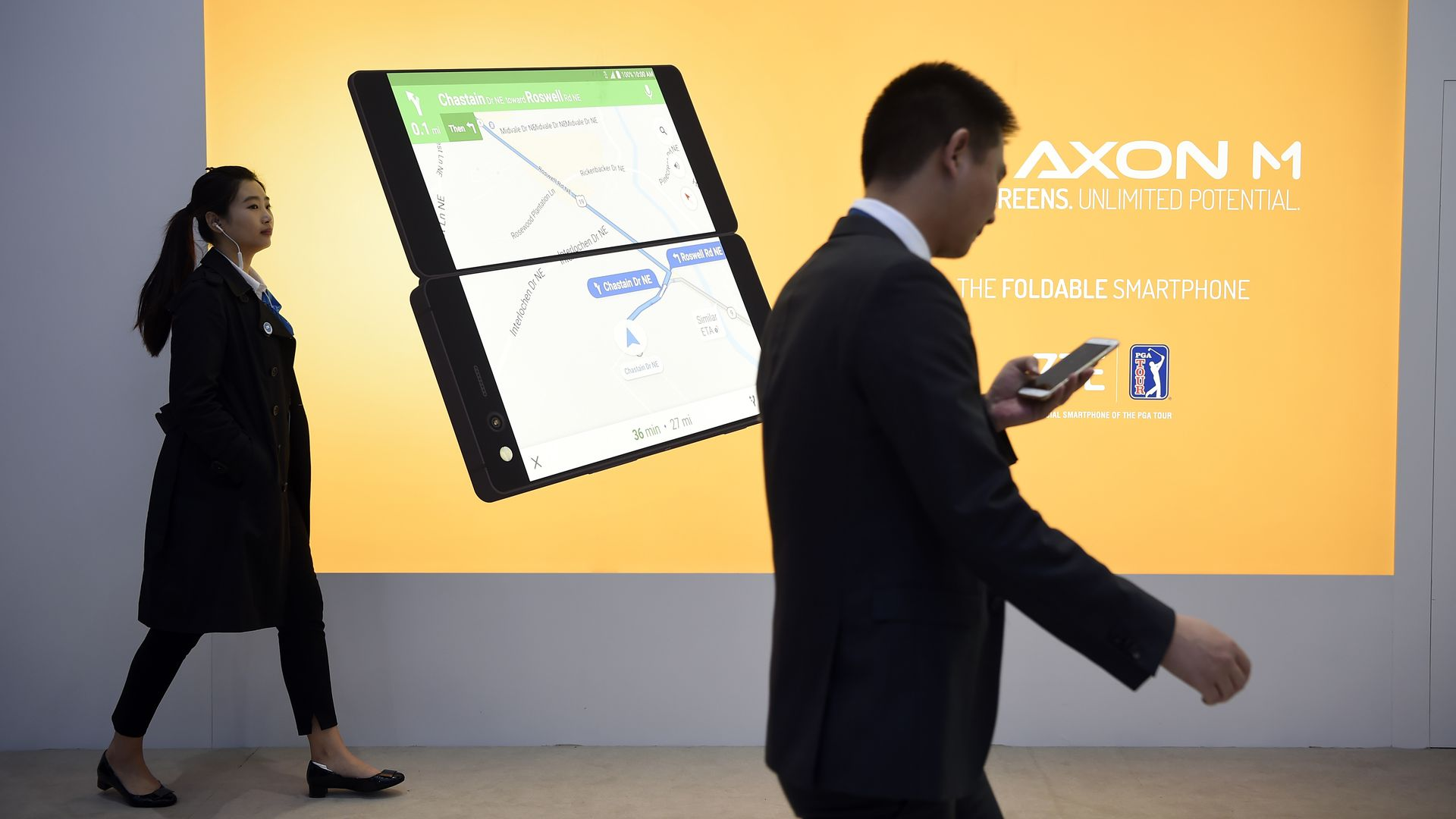 Two people walk past a billboard announcing the new ZTE's dual screens foldable smartphone AXON M