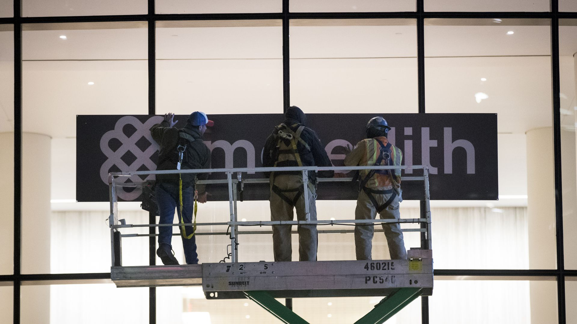 Meredith workers replace the old Time Inc. logo.