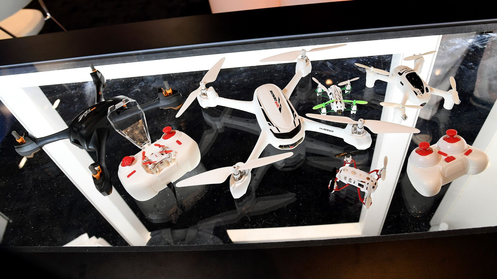 A table with remote controlled drones on them.