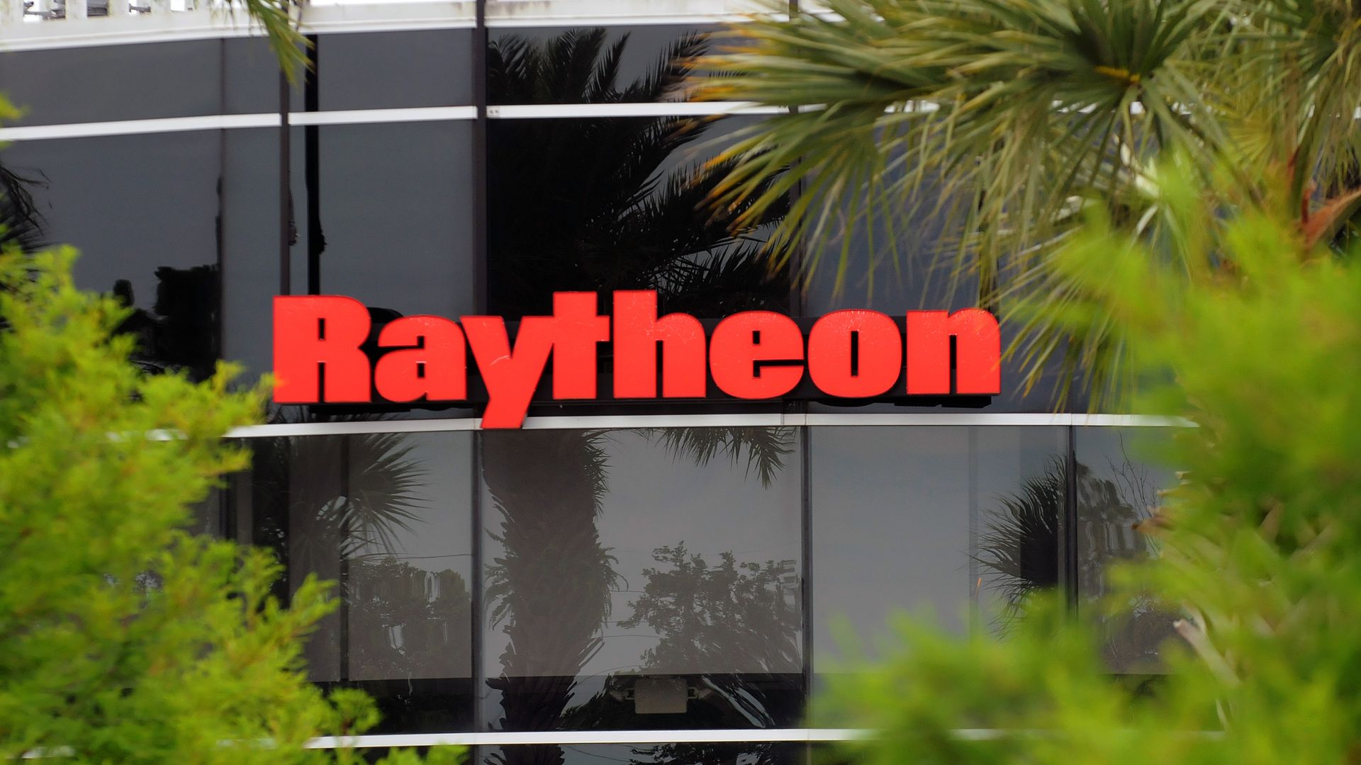 In this image, the Raytheon logo is seen on the side of a glass building, framed by trees.