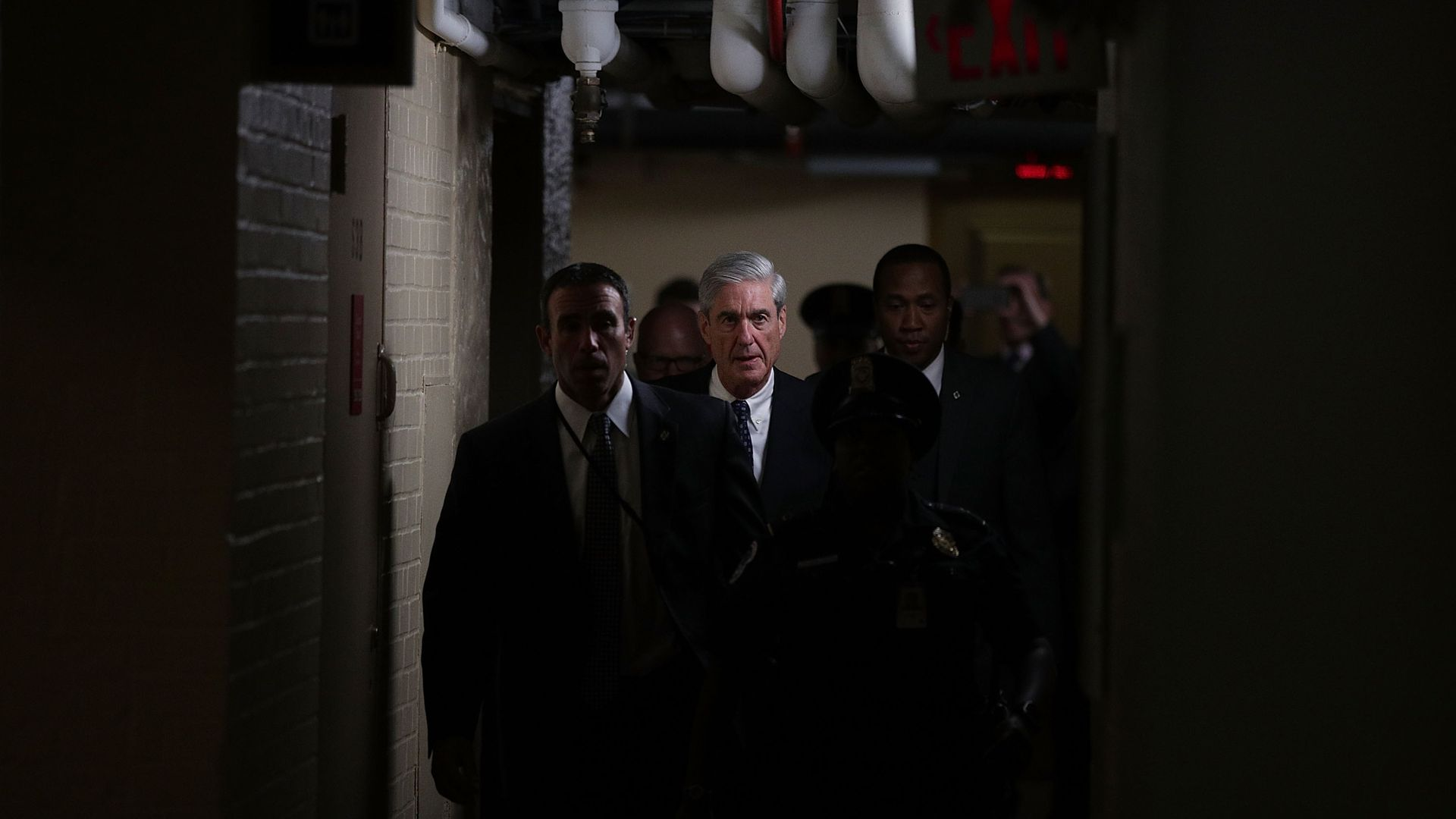 Robert Mueller walks with a group of people through a dark hallway.