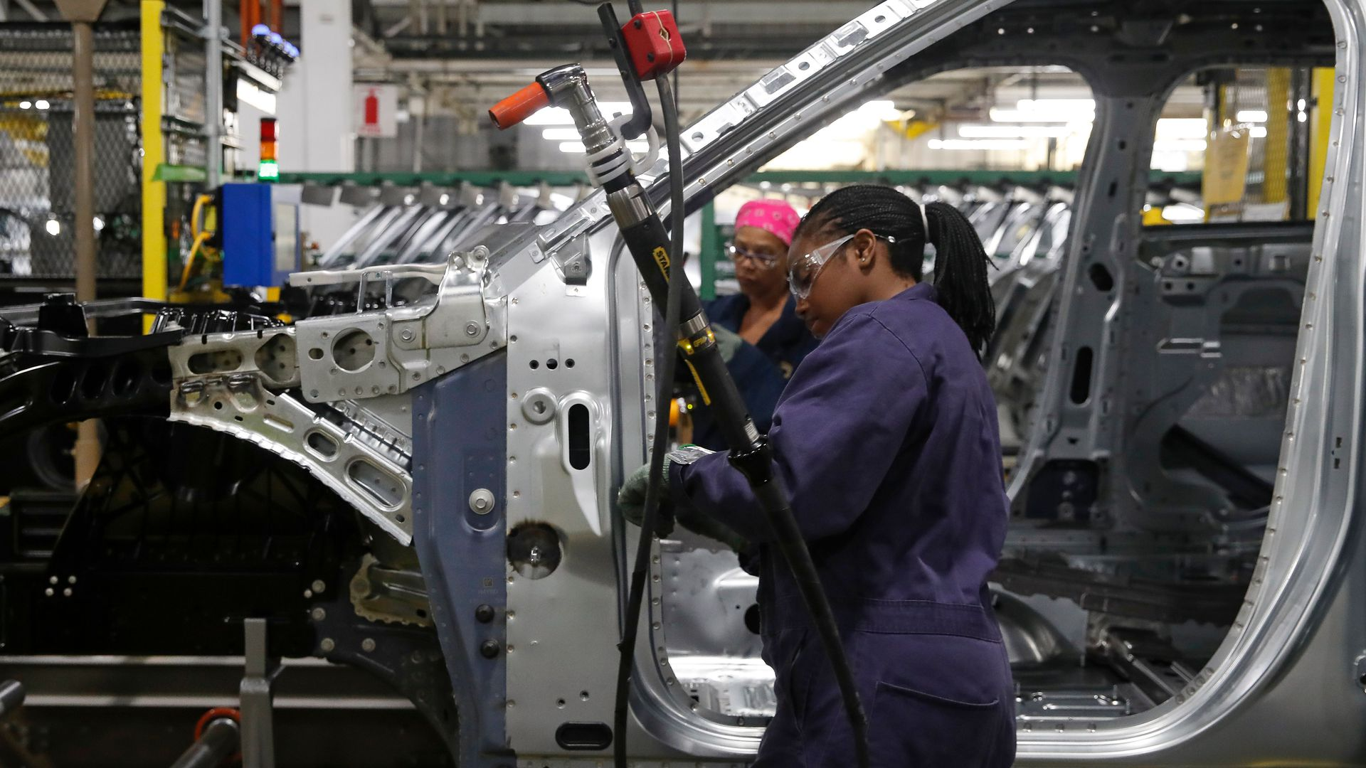 Workers assemble cars at the newly renovated Ford's Assembly Plant in Chicago,