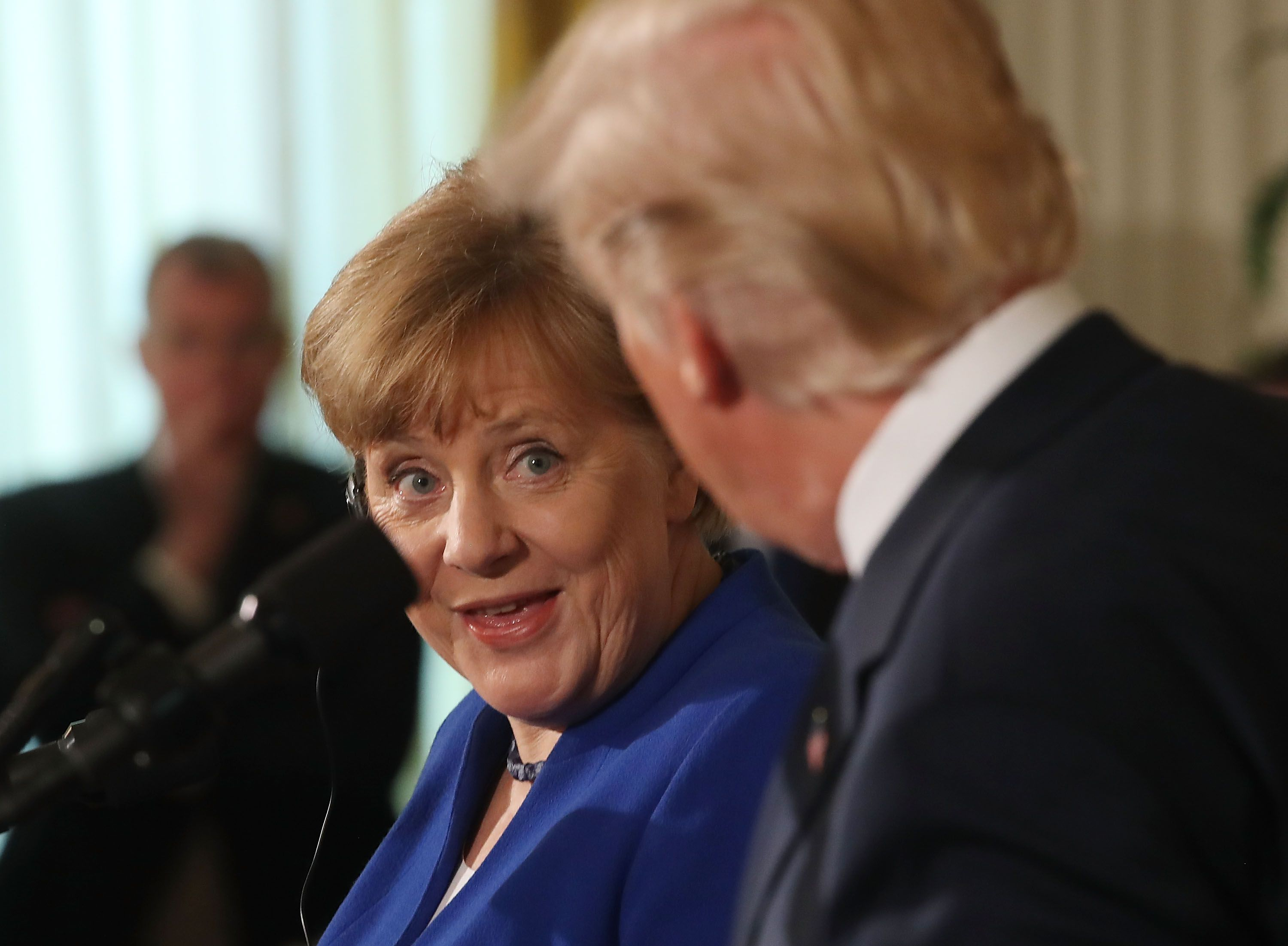 Merkel looks at Trump with surprised expression, mouth agape.