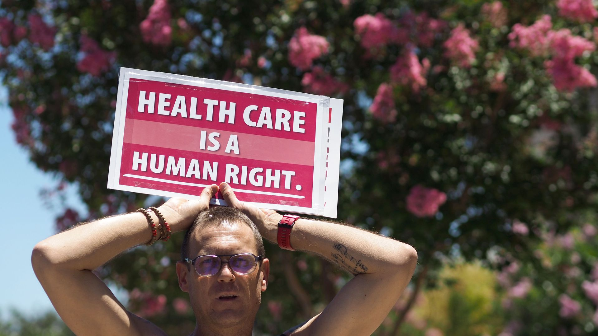 "A man holds a sign that reads, ""Health care is a human right."""