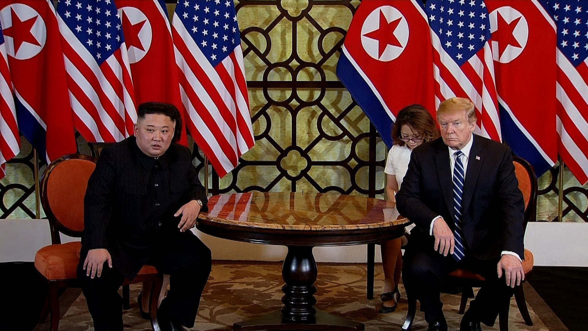 In this image, Donald Trump and Kim Jong Un sit across from each other at a round wooden table, with the American and North Korean flags draped behind them.