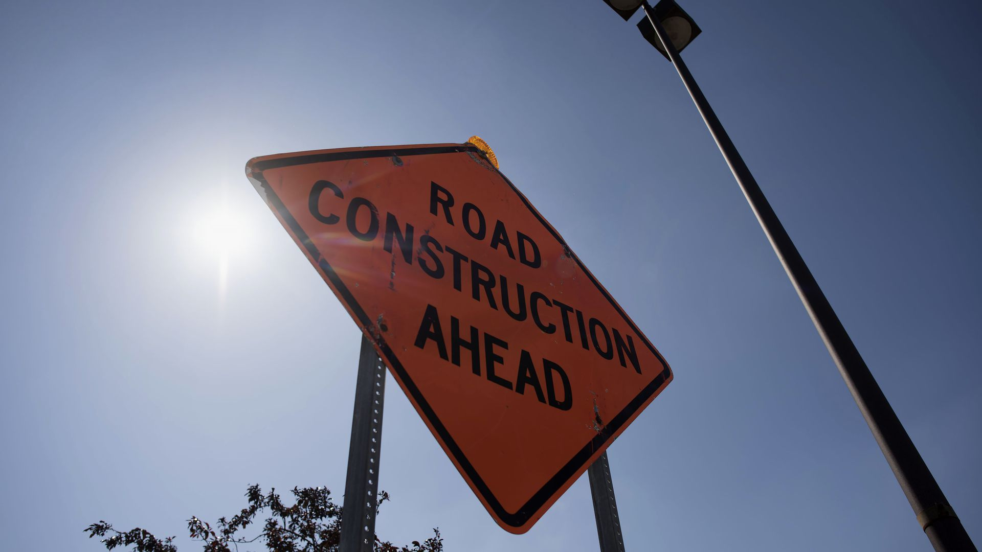 A sign warning of road construction ahead.