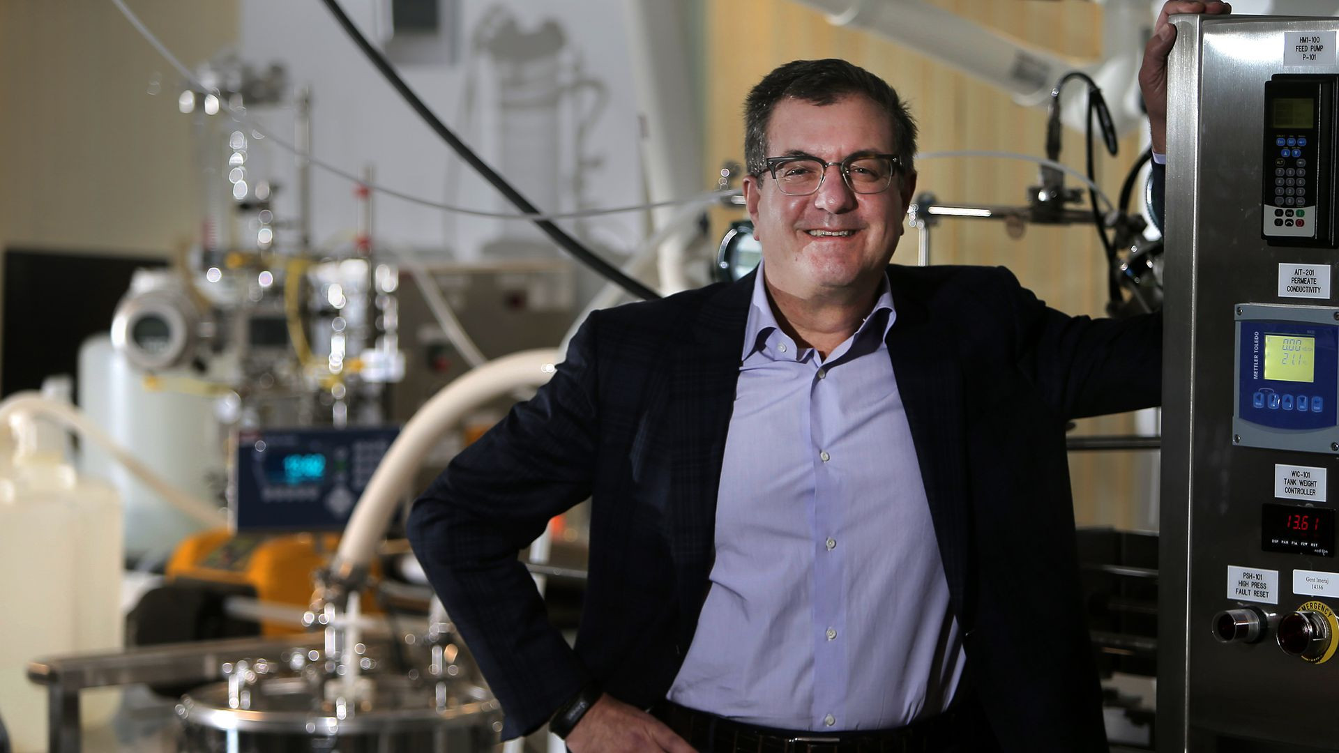 Alnylam CEO Dr. John Maraganore poses for a portrait with lab equipment behind.