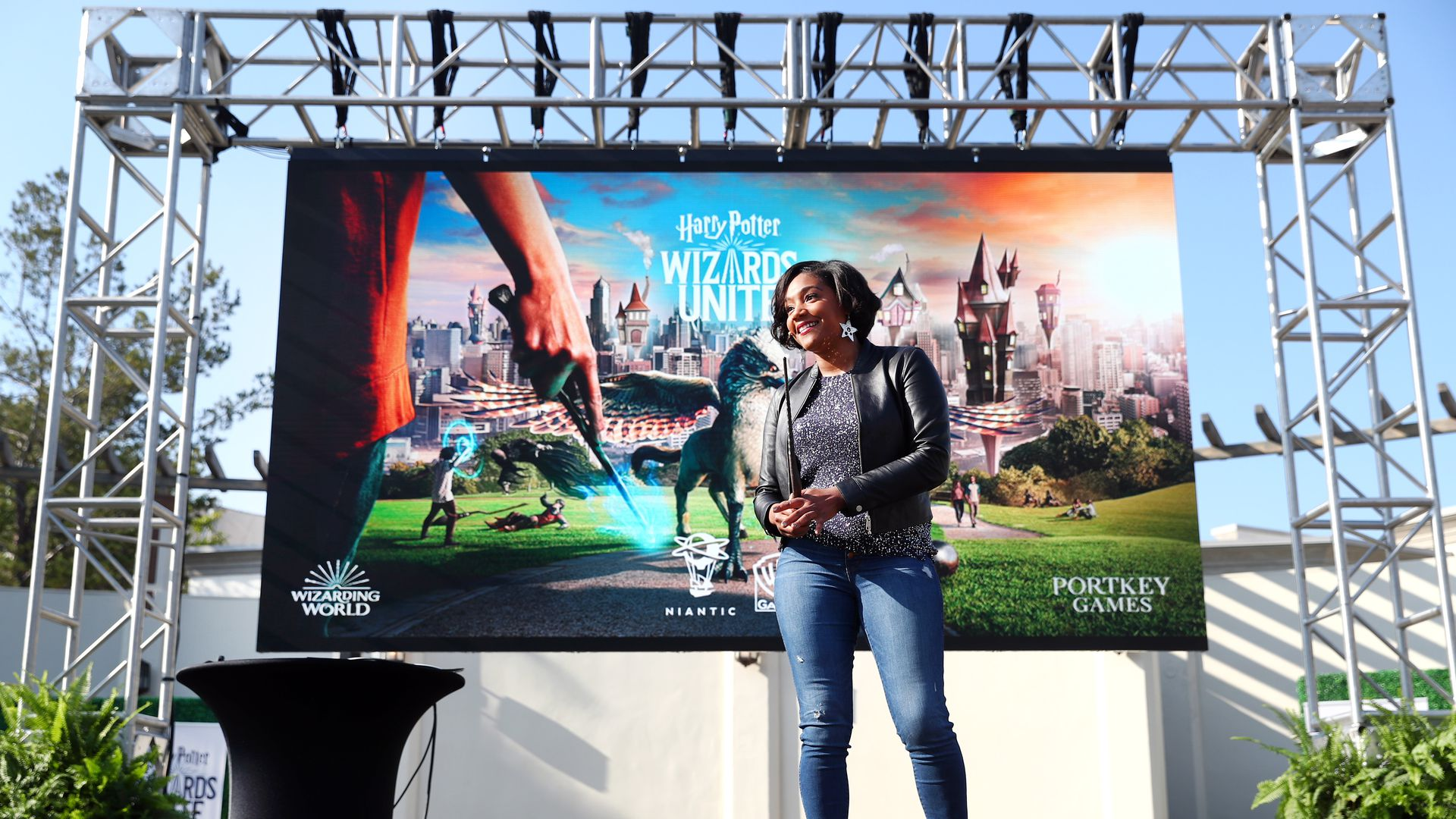 In this image, Tiffany Haddish stands outside on stage with the poster for Wizards Unite behind her.