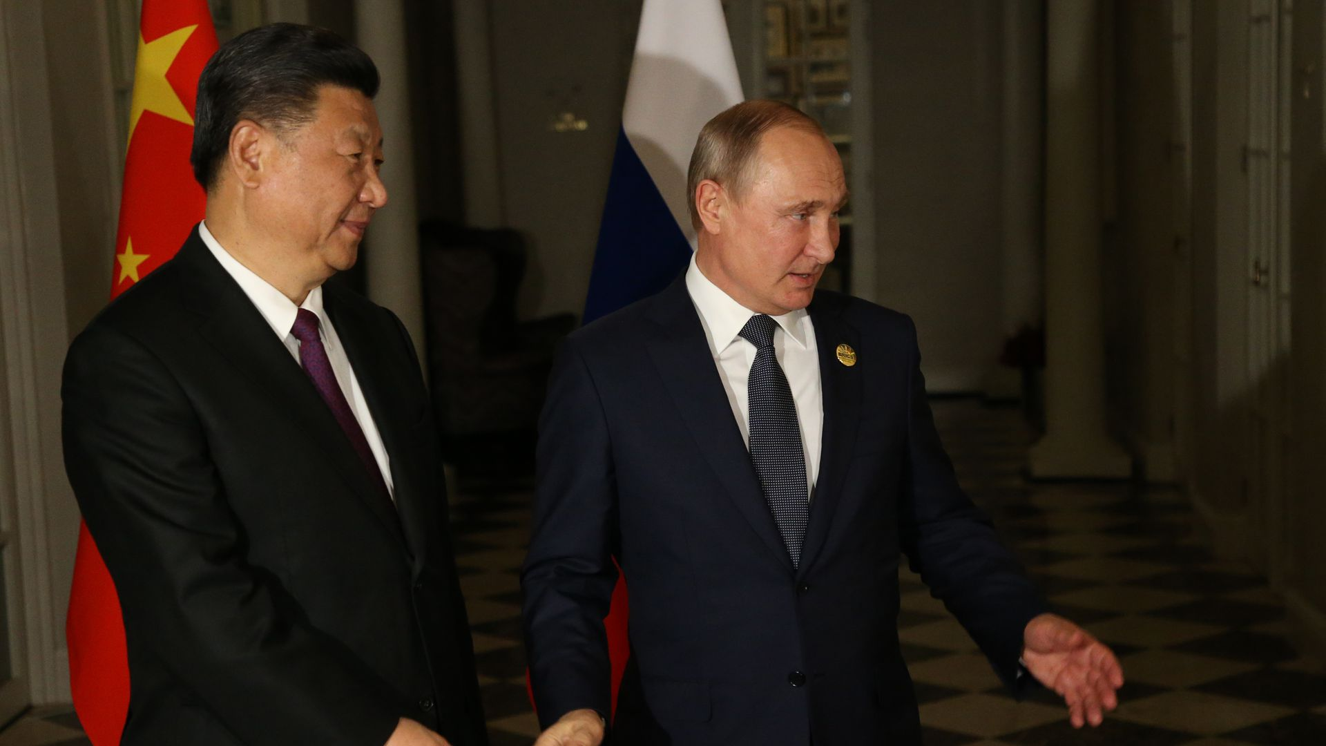 Chinese president Xi Jinping stands next to Russian president Vladimir Putin in front of both countries' flags