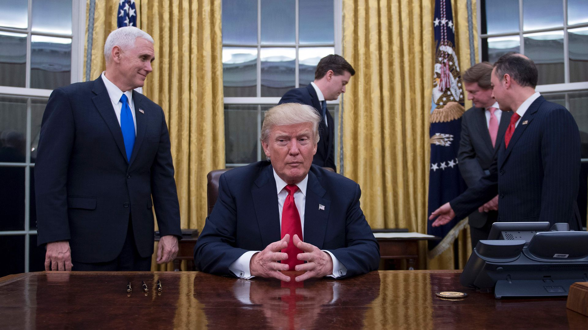 Donald Trump sits at his desk as his staff works around him