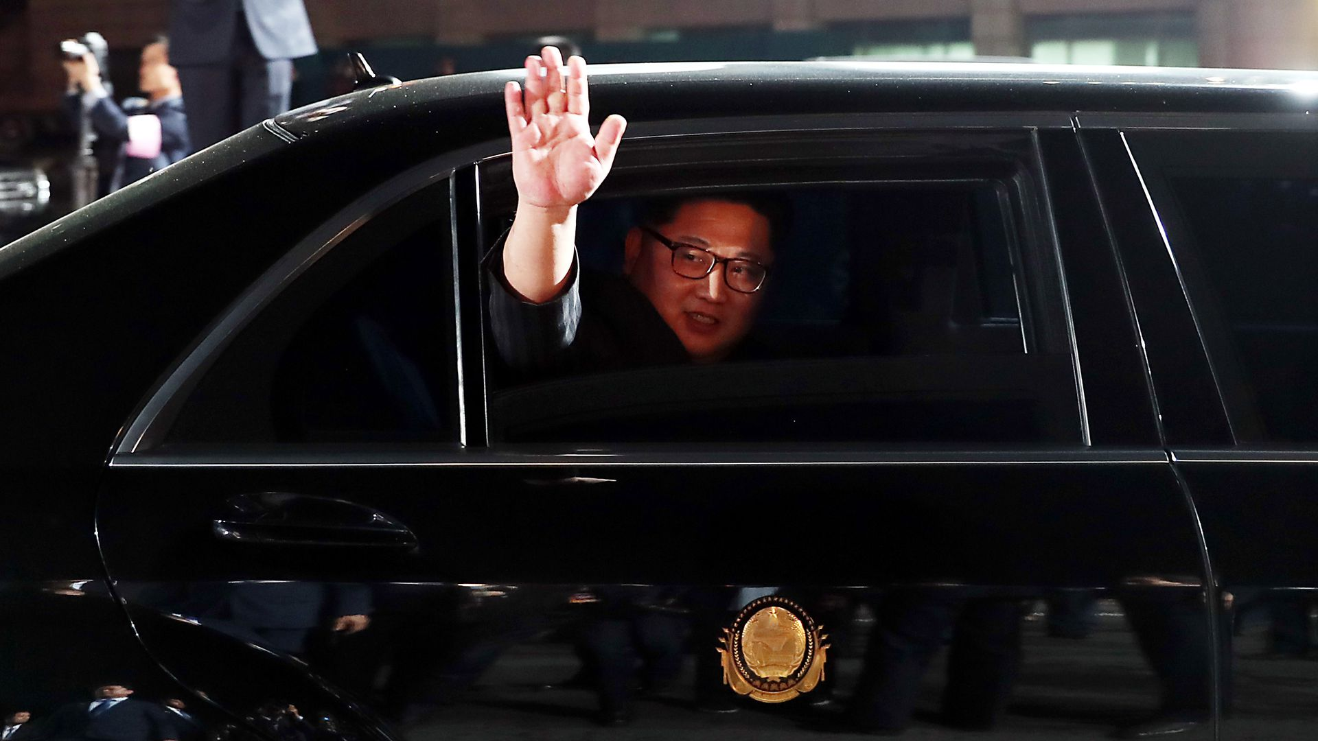 Kim Jong-un waves from a black limo.