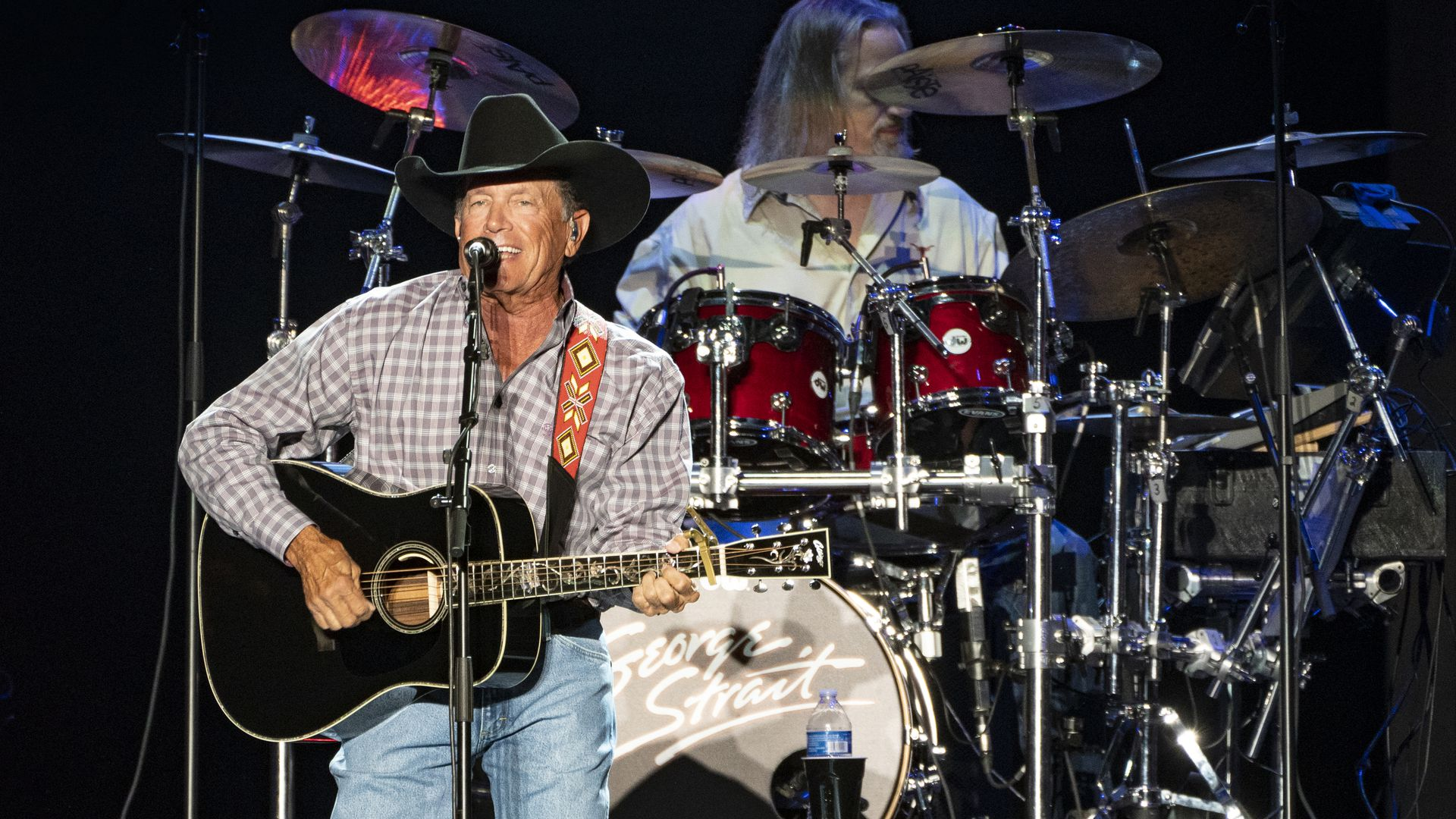 George Strait singing with a guitar in hand