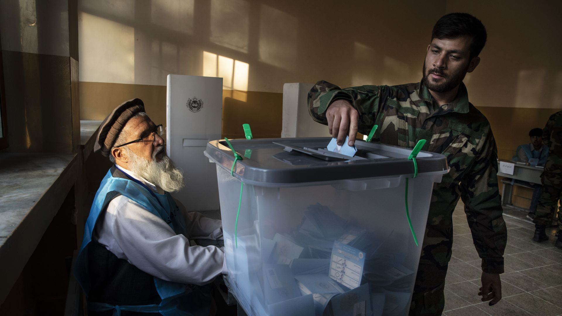 Afghan soldier submits his vote at a polling place