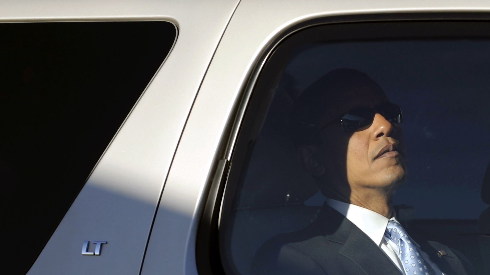 Obama wears sunglasses in the back seat of a car