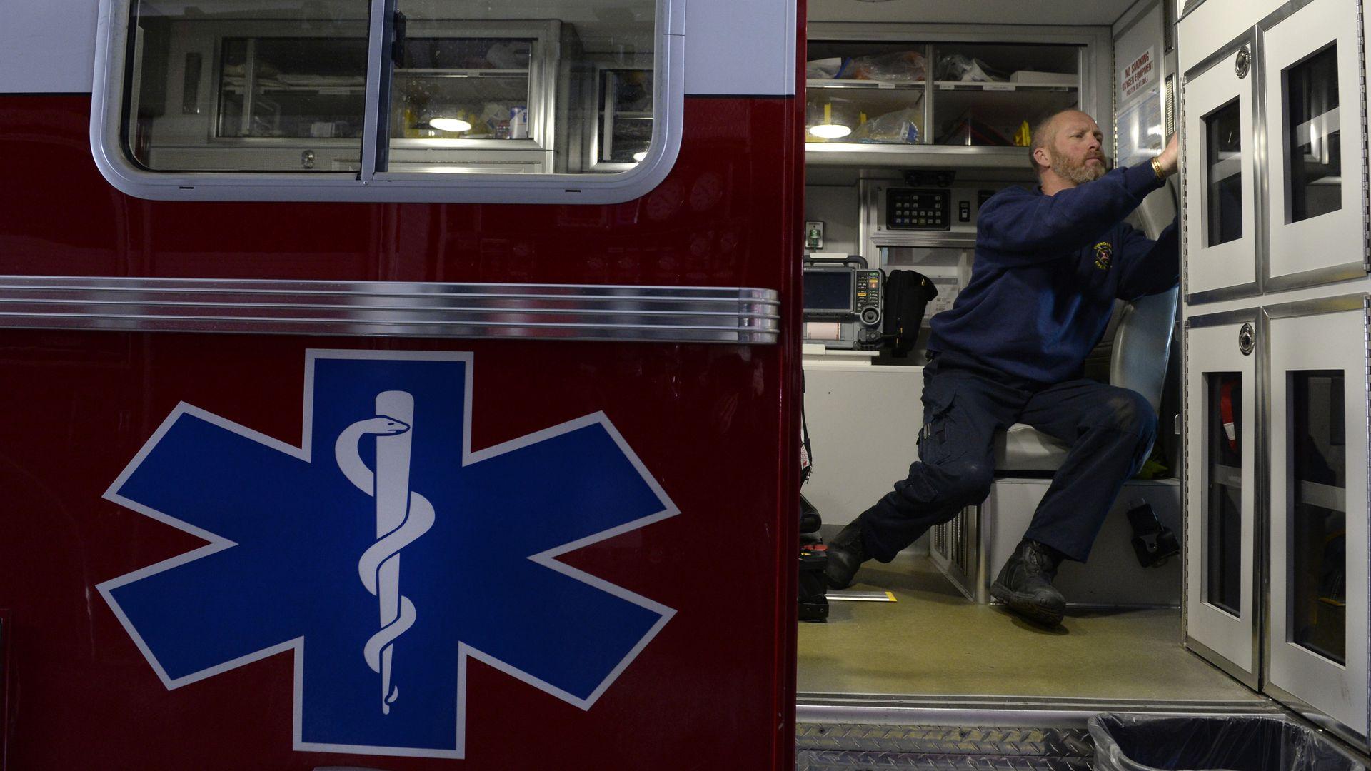 A paramedic prepares an ambulance for upcoming calls.