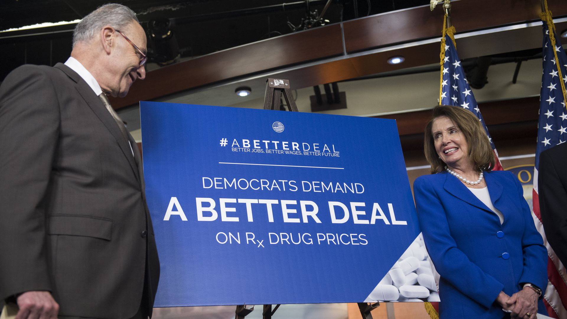 Schumer and Pelosi next to a drug price sign