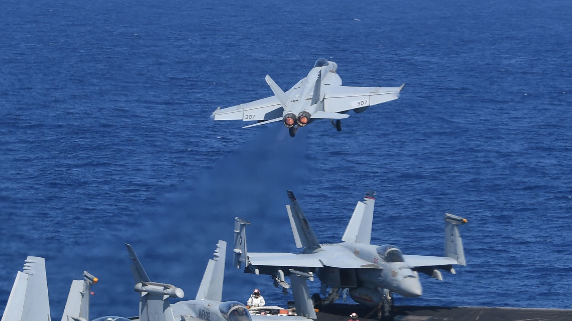 F18 fighter jet takes off from aircraft carrier