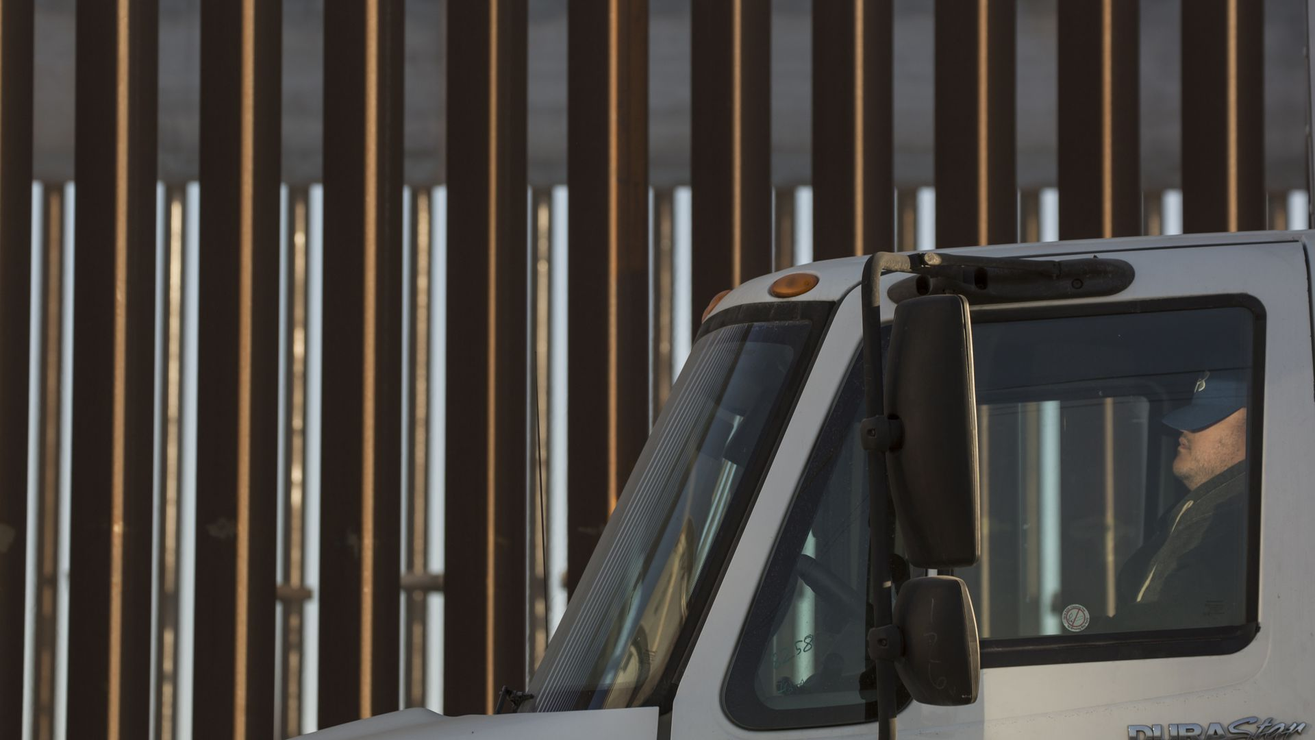 A truck in front of the border wall.
